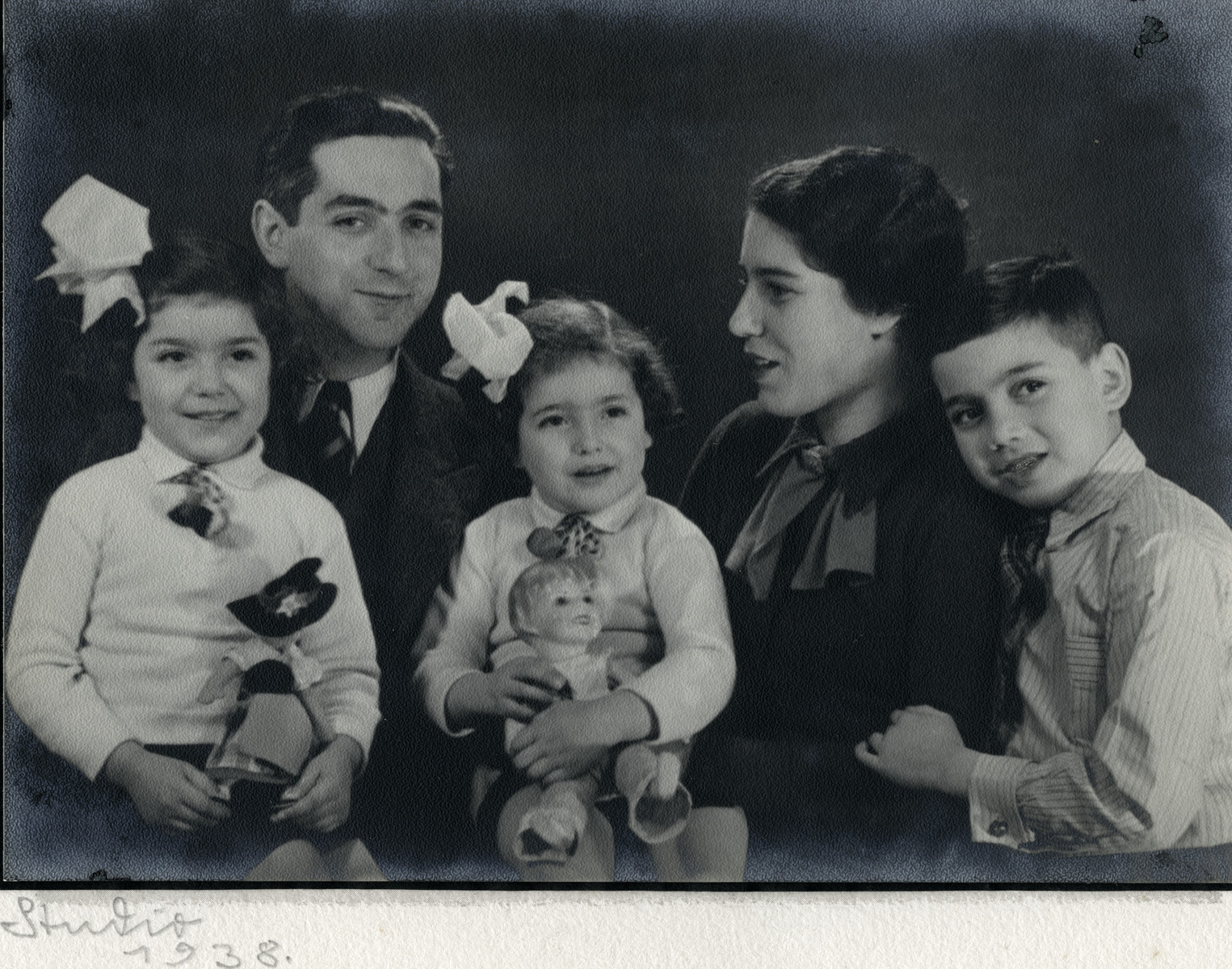 Studio portrait of a Dutch Jewish family.   From left to right are Ruth, Alexander, Naomi, Frederika and Elchanan Tal.