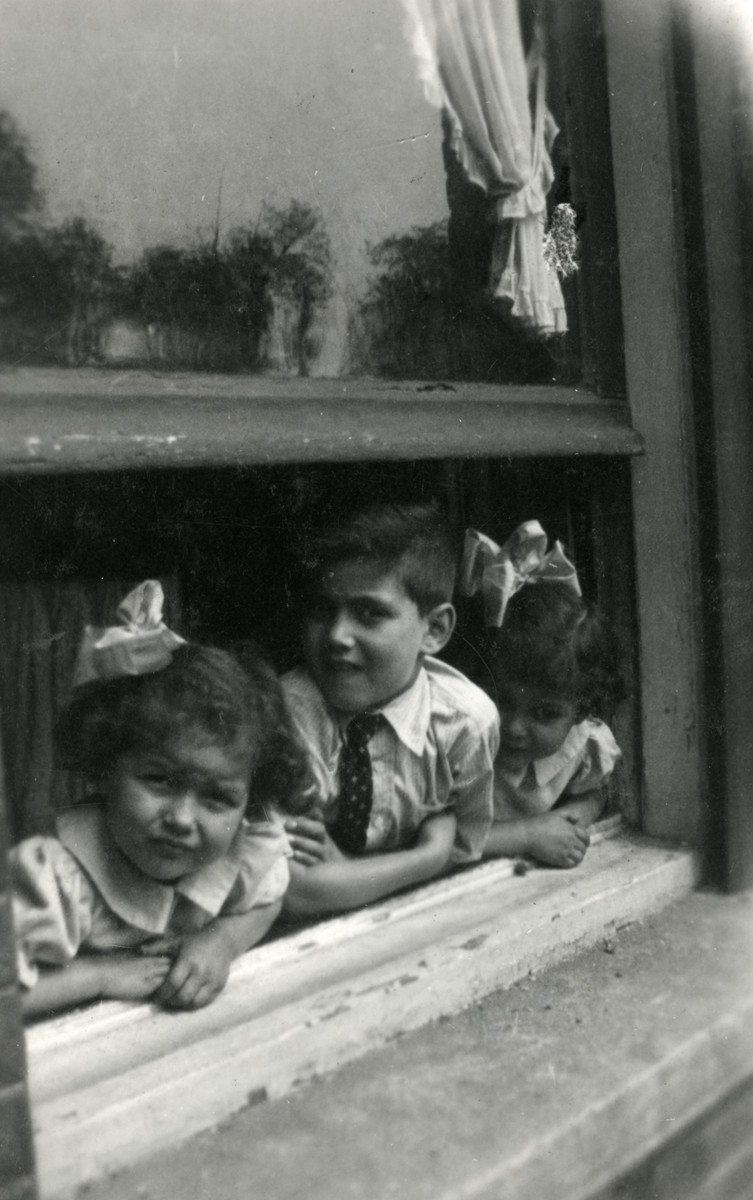 Elchanan, Ruth and Naomi Tal look out the window of their home.