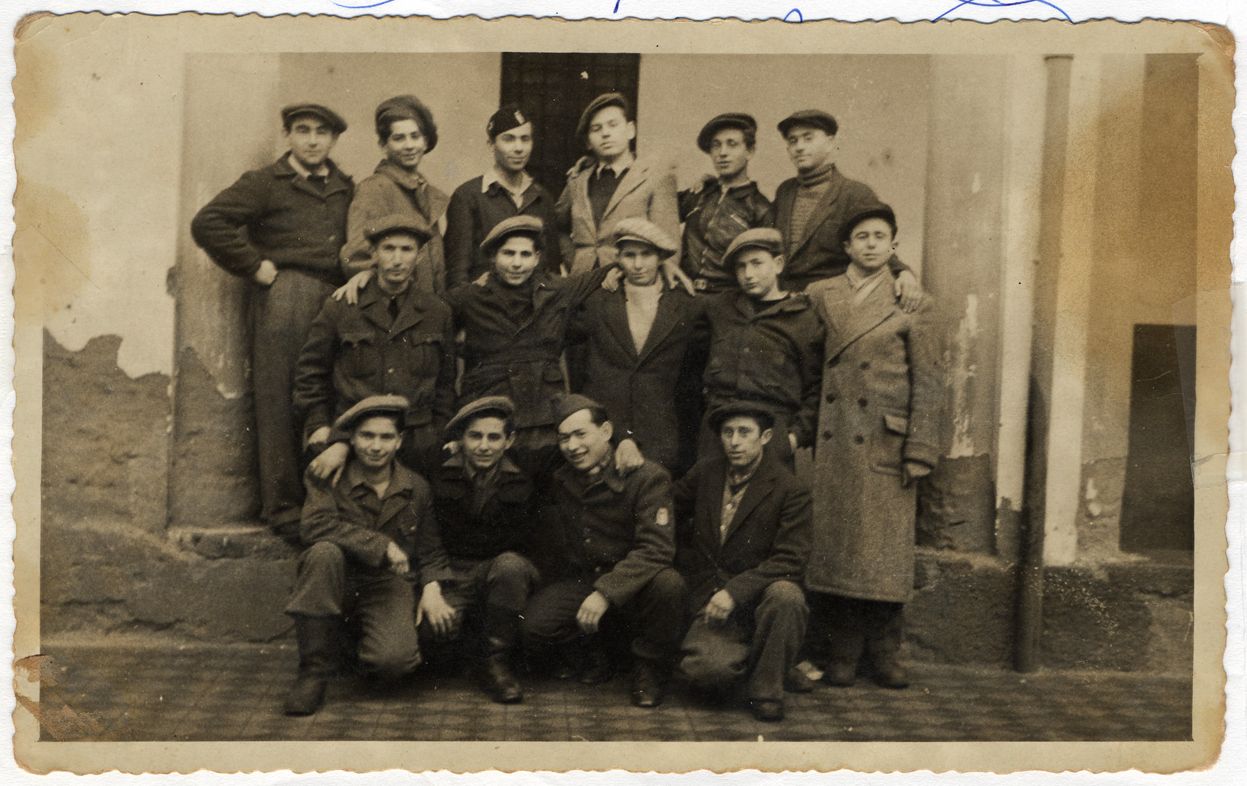 Group portrait of displaced persons in Kibbutz Mekor Baruch, a Poal Mizrachi fishing hachshara in Bacoli, Italy.  Pictured from left to right are (first row): Meir Weiss, unknown, Ben-Zion Gasner, and unknown; (second row) Mangel, Eliezer Majerovic, Shmuelevitz, Shmuelevitz and Moshe Fruchter; (third row): Moshe Bergerm Mordechai Feld, David Weiss, Zvi Rengel, unknown, and Yona Kalosh.