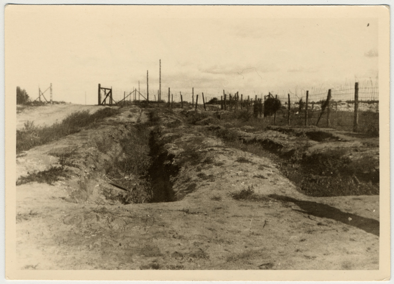 "View of a mass grave pictured after the liberation of Bergen-Belsen.  The original caption states, ""Graves that had been dug up to bury the prisoners as they died. They died so fast and there were so many that it was hard to keep up with them."""