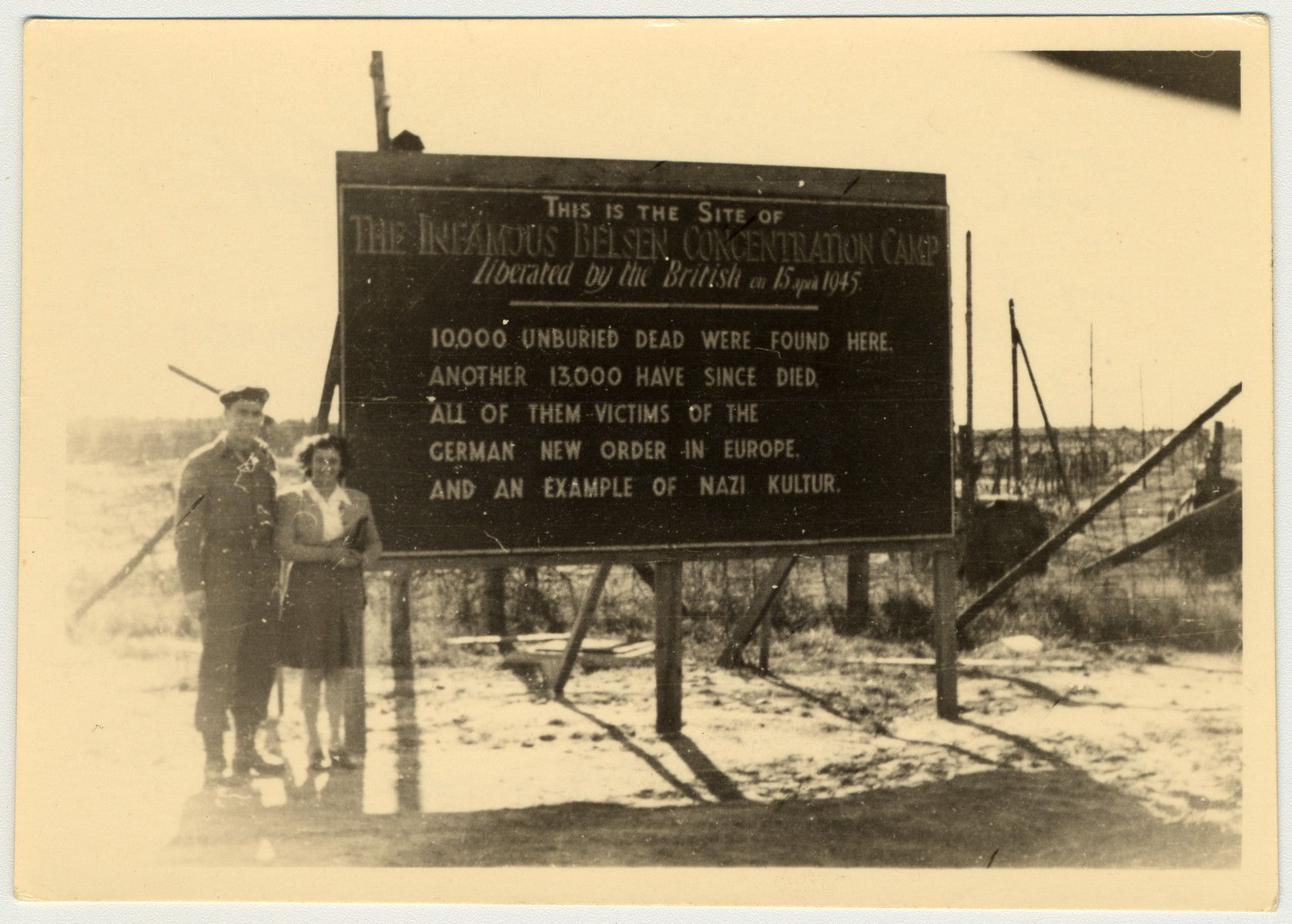 "A former prisoner of Bergen-Belsen stands with a British sergeant next to a sign marking the site of Bergen-Belsen after the liberation of the concentration camp on April 15, 1945.  The original caption states, ""The girl and the Sgt. The girl was a prisoner there in Belsen and was very lucky to come out alive. She showed us around the camp.""  The sign was created by Arthur Reginald Price, a signwriter who was serving with the 113th Durham Light Infantry. His regiment arrived at Bergen Belsen on April 17, two days after its liberation. There, Price was tasked with producing signs for a film crew to help document the scenes, as they had no sound recording available, as well as to mark the graves and to ensure that troops were aware of the Typhus outbreak. His signature, ""Price,"" may be seen in the upper right corner."