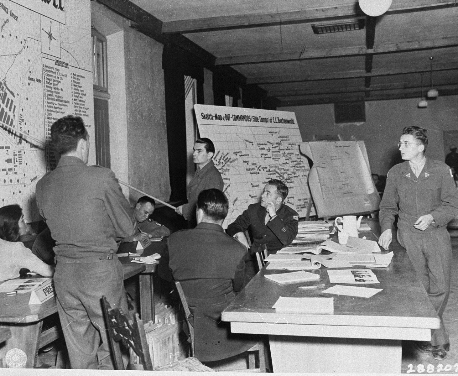 Wolfgang Otto, a former SS Sergeant, answers questions during the trial of 31 former camp personnel and prisoners from Buchenwald by indicating a spot on a map of the camp where prisoners were murdered.    Pictured on the far right is the interpreter Herbert Rosenstock, while sitting at the table with their backs to the camera are American lawyers Sol Surowitz (left) and Robert Kunzig.