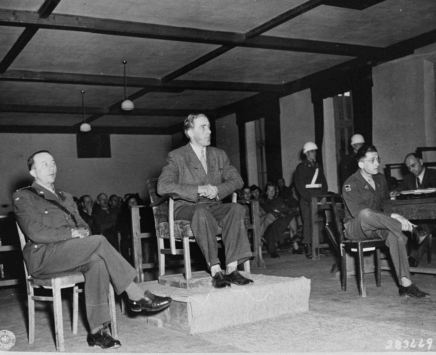 Aksel Frydenabjerg, a member of the Criminal Intelligence Division in Denmark, testifies at the trial of former camp personnel and prisoners from Buchenwald.  To his left is Captain Regner P. Mortensen, a Danish liaison officer and interpreter, and on the right is Herbet Rosenstock, another interpreter.