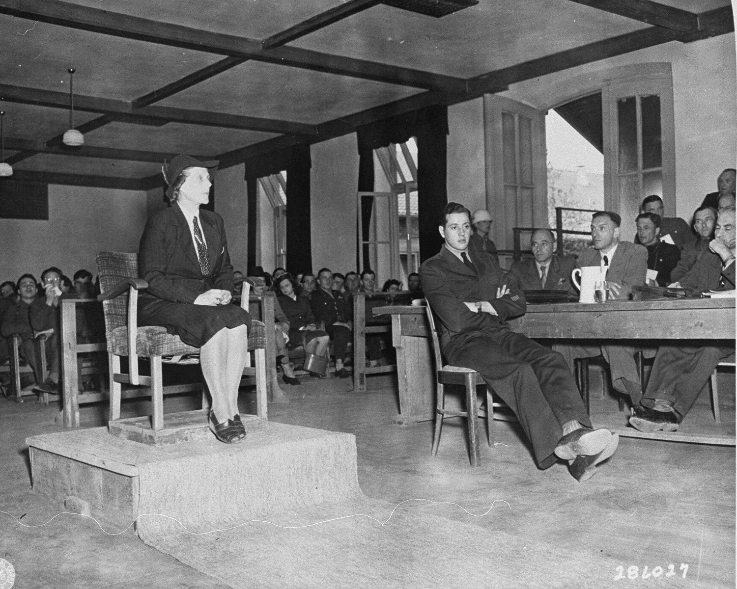 Maria Gersheim, a witness for the prosecution, testifies at the trial of former camp personnel and prisoners from Buchenwald.  On her left is Fred Stecker, a German interpreter.