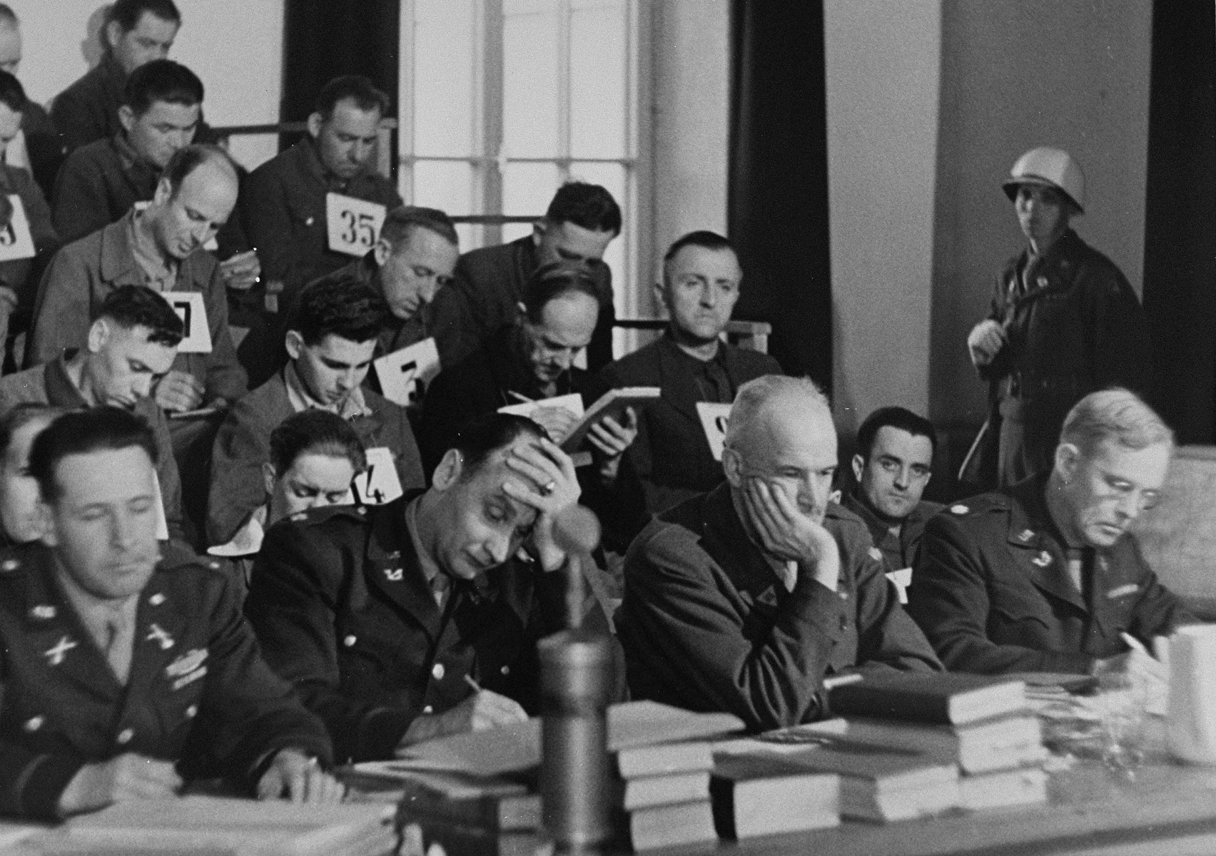 The defendants in the trial of 61 former camp personnel and prisoners from Mauthausen sit behind a group of American military lawyers, who have been assigned to defend them.