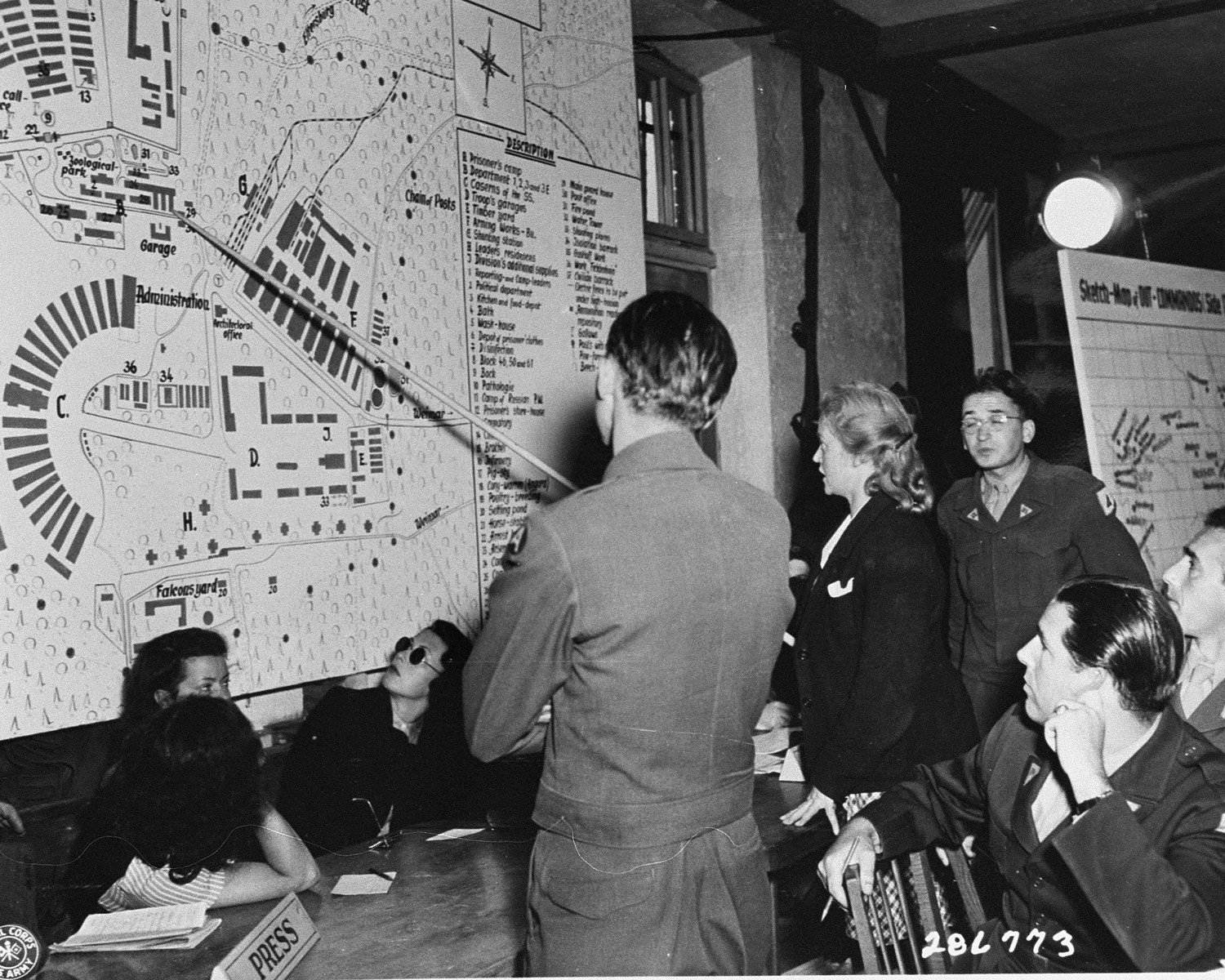 Ilse Koch points out places she visited in Buchenwald, at the trial of former camp personnel and prisoners from Buchenwald.    Among those pictured is William Denson (to Koch's left, with back to the camera), chief American prosecutor; and Herbert Rosenstock (to Koch's right), an interpreter.