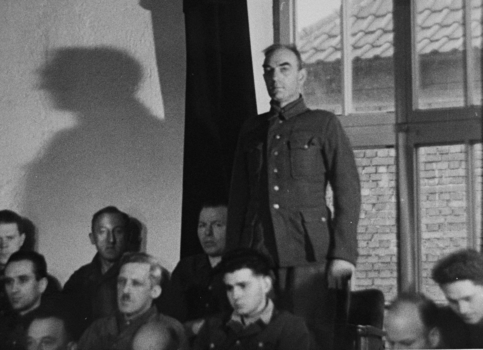 August Blei, a defendant at the trial of 61 former camp personnel and prisoners from Mauthausen, stands in his place in the defendants' dock.