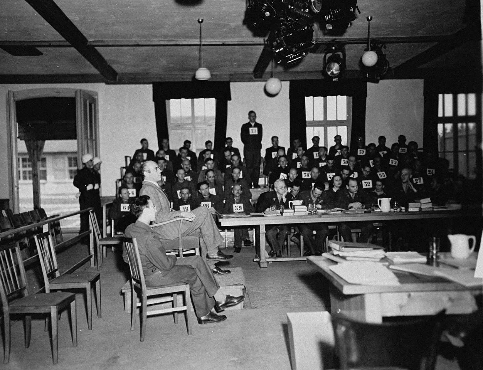 A witness testifies at the trial of 61 former camp personnel and prisoners from Mauthausen.    Standing in the defendants' dock at back is August Eigruber, former Gauletier of Upper Austria.