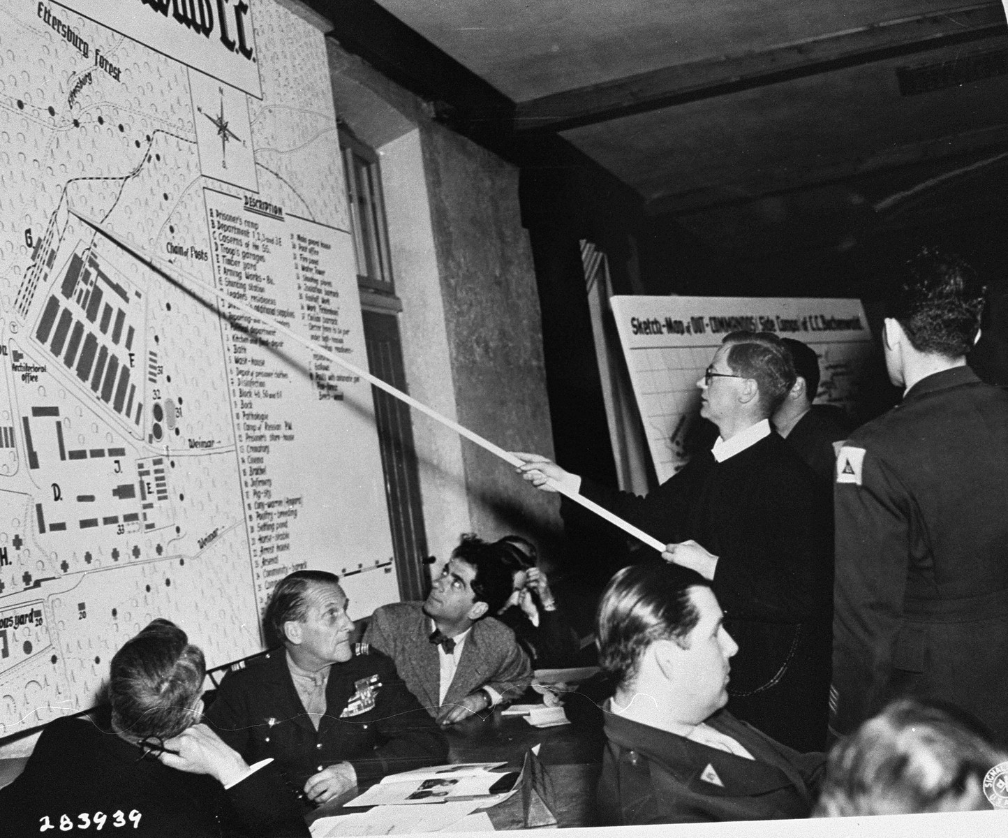 Father Jean Brinioul, a witness for the prosecution, indicates on a map where he was forced to work, during the trial of former camp personnel and prisoners from Buchenwald.    Looking on are George Converse of the Western Defense Command; Sol Surowitz, an American prosecutor; and Fred Stecker, an interpreter.