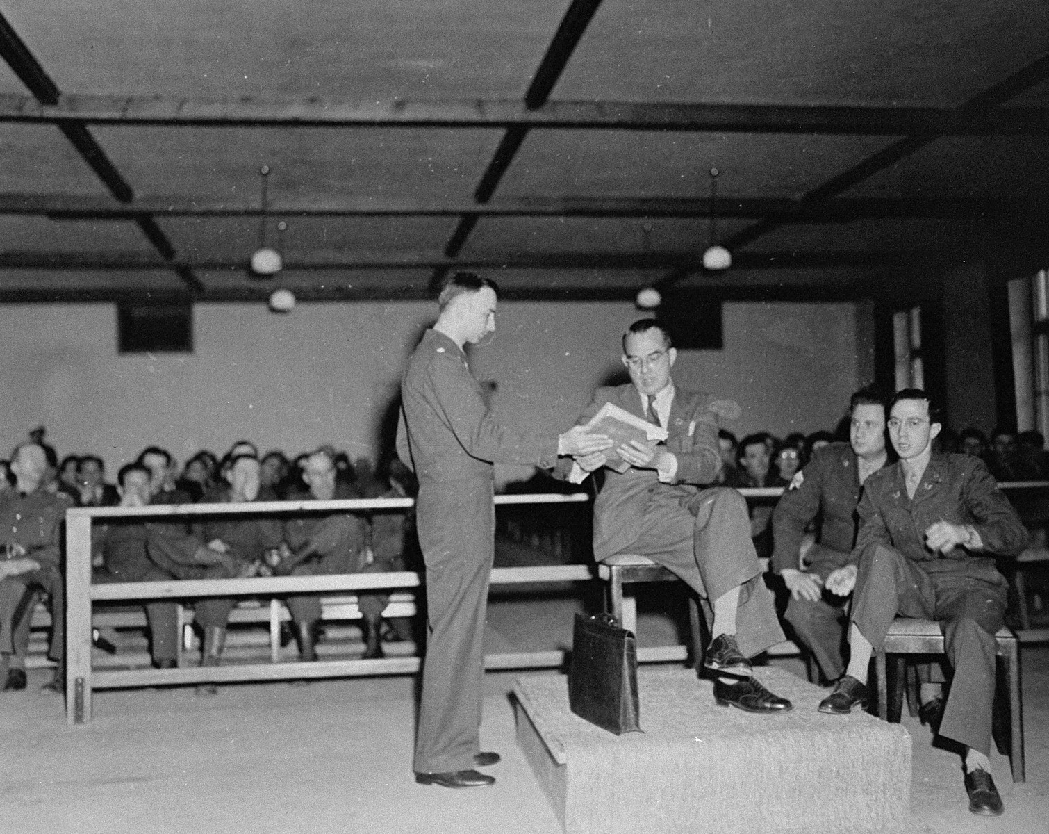 A witness testifies at the trial of 61 former camp personnel and prisoners from Mauthausen.    Pictured on the left is U.S. prosecutor William Denson.