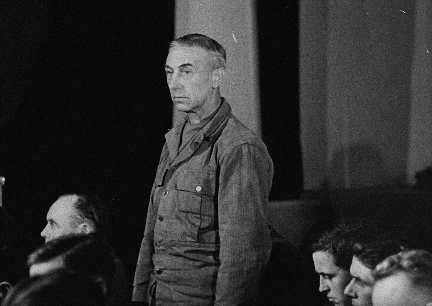 A defendant at the trial of 61 former camp personnel and prisoners from Mauthausen, stands in his place in the defendants' dock.    The defendant is probably Julius Ludolf, a former Lieutenant in the SS and the commandant of Melk.