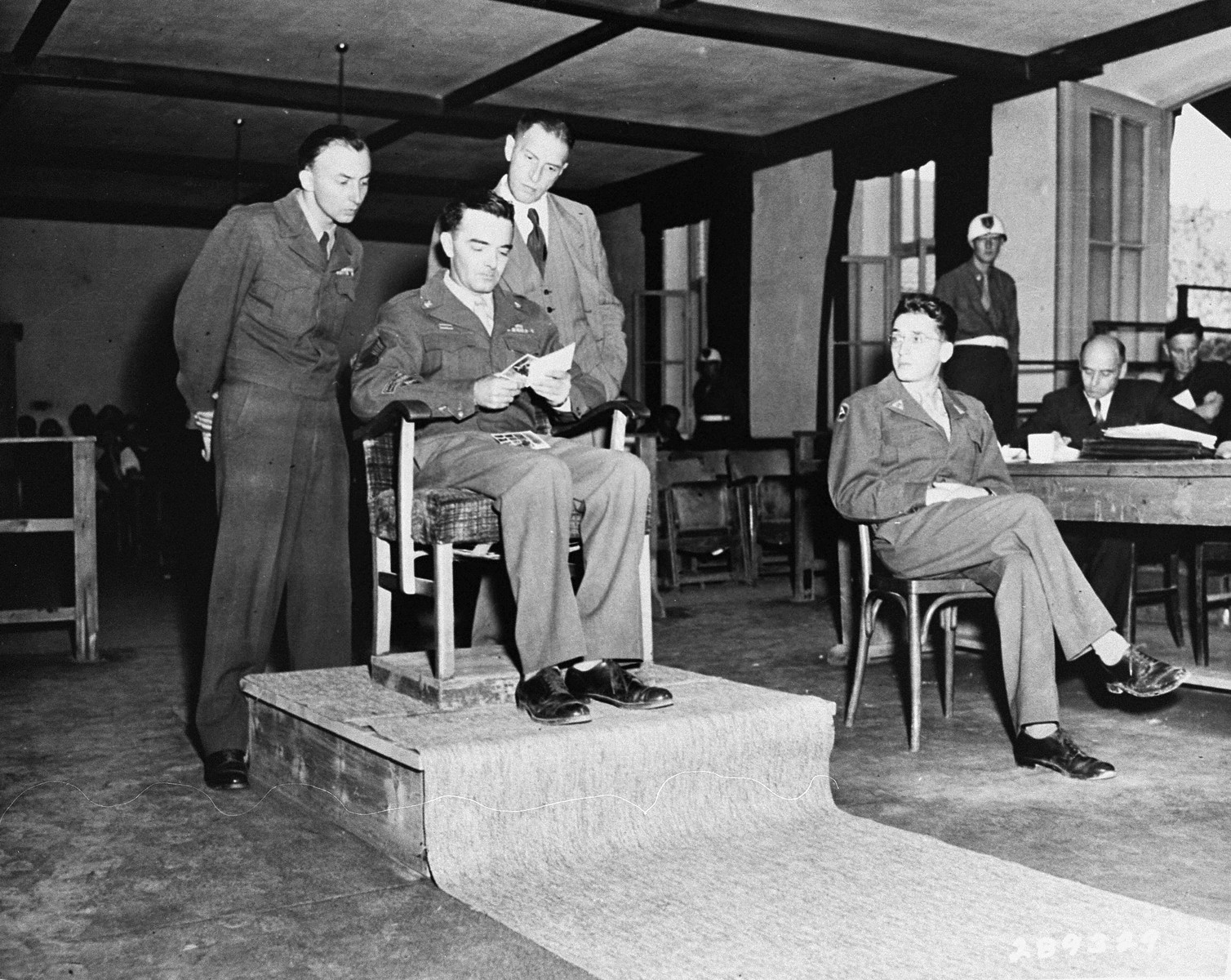 Technical Sergeant Adrian Robertson, a photographer with the U.S. Army Air Corps, identifies photographs from the liberation of Buchenwald as a witness for the prosecution at the trial of former camp personnel and prisoners from the Buchenwald concentration camp.    Court personnel pictured from left to right are: U.S. Chief Prosecutor William Denson; Technical Sergeant Robertson; defense attorney Dr. Richard Wacker; and interpreter Herbert Rosenstock.