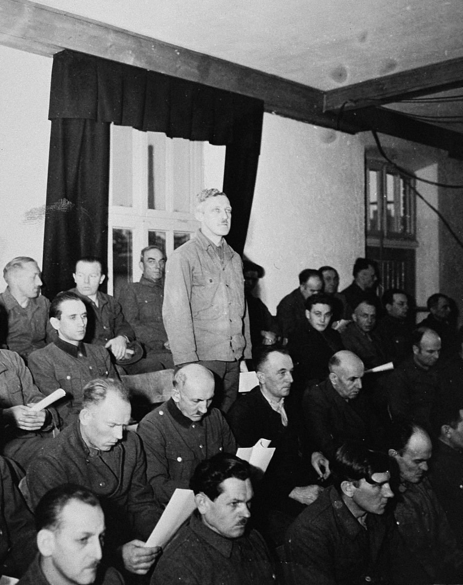 August Eigruber, former Gauleiter of Upper Austria, a defendant at the trial of 61 former camp personnel and prisoners from Mauthausen, stands in his place in the defendants' dock.    Eigruber was convicted and sentenced to death on May 13, 1946.