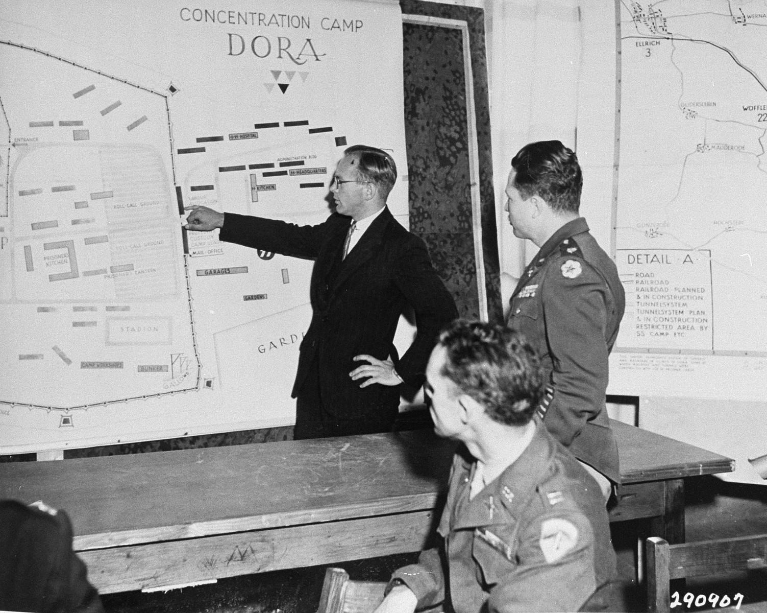 Tadeusz Patzer, a prosecution witness from Poland, points out the location of the labor allocation offices at Nordhausen, during the trial of former camp personnel and prisoners from Dora-Mittelbau.    Patzer had been a political prisoner at Auschwitz, Buchenwald, and finally Nordhausen.  Looking on are defense counsel Major Leon G. Poullada (right) and assistant prosecutor Captain William F. McGarry (foreground).
