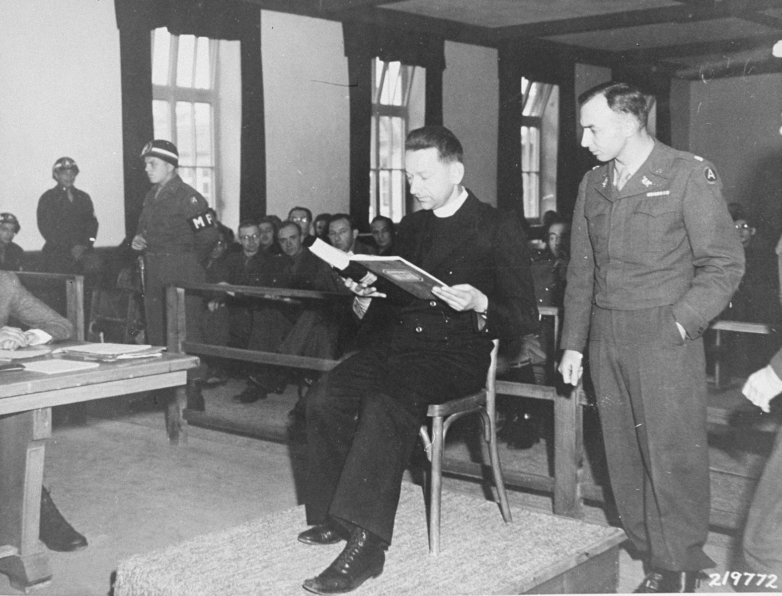 Polish priest Theodore Korcz reads to Lt. Colonel William Denson from a camp medical record presented as evidence at the trial of former camp personnel and prisoners from Dachau.    The log recorded the deaths of several Catholic priests who were used as subjects in malaria experiments.