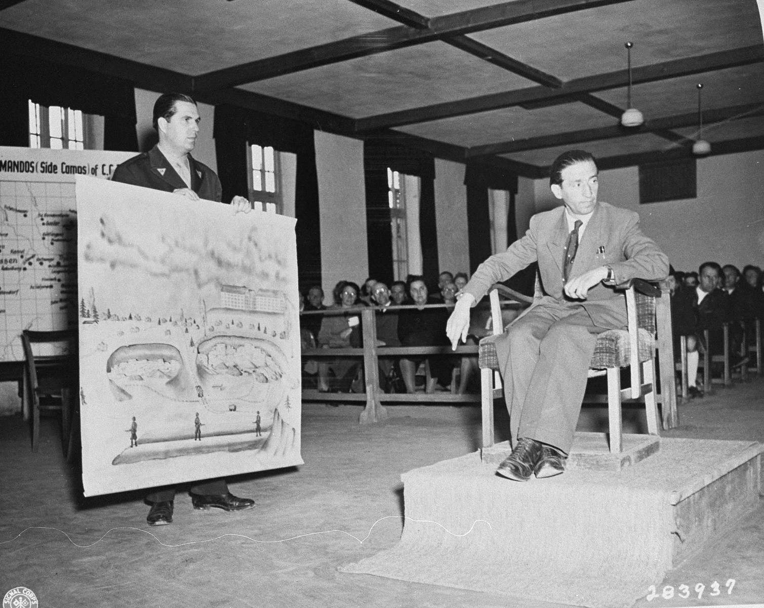 Kurt Rosener, a witness for the prosecution, identifies a drawing of a stone quarry for the prosecution at the trial of former camp personnel and prisoners from Buchenwald.    To his right is Robert Kunzig, one of the American prosecutors.