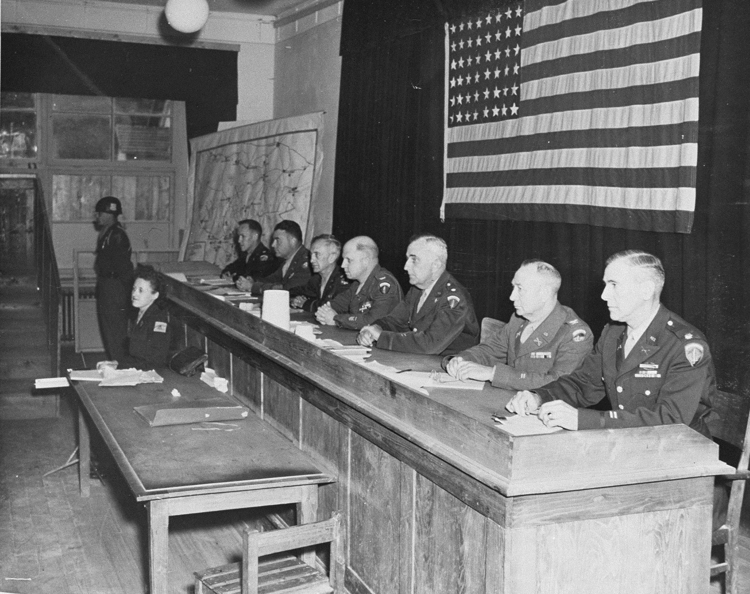 The judges comprising the American Military Tribunal which presided over the Dora-Mittelbau war crimes trial.  The officers' names, from left to right, are: Major W. M. Vanderburgh, Lt. Colonel L. S. Tracy, Colonel Joseph W. Benson, Colonel Frank Silliamn, III, Lt. Colonel David H. Thomas, Colonel Claude O. Bunch, and Lt. Colonel Roy J. Herte.