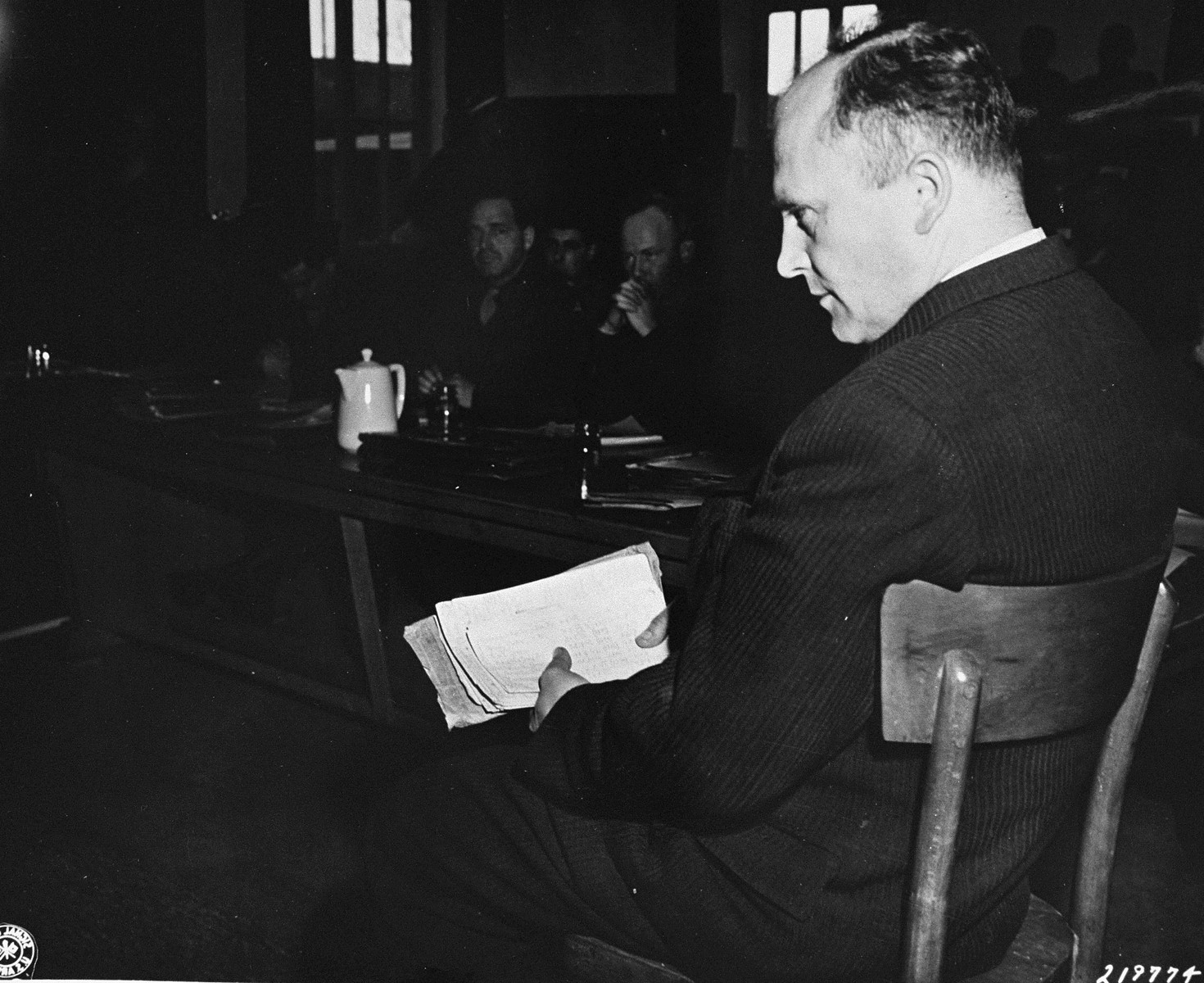 Friedrich Hoffman, a Czech priest, testifies at the trial of former camp personnel and prisoners from Dachau.  In his hand he holds a packet of records that show that 324 priests died at the camp after being exposed to malaria during Nazi medical experiments.