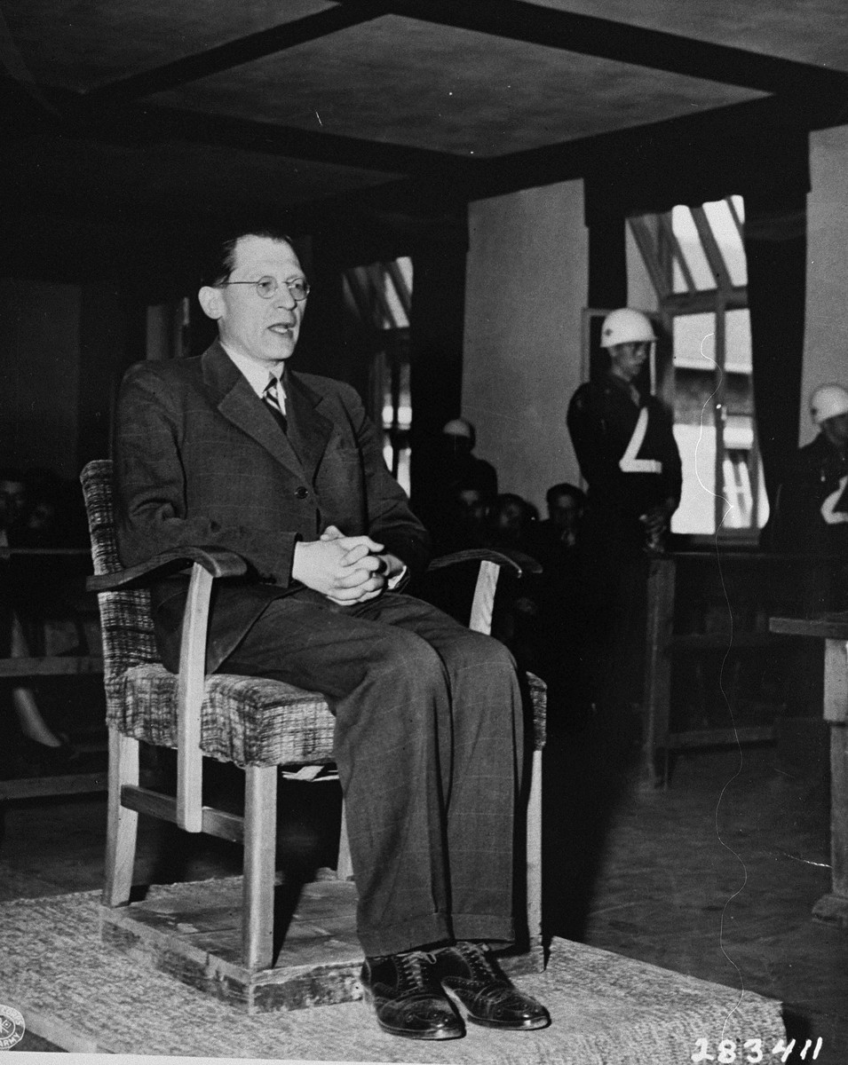 "Dr. Eugen Kogon, a former Austrian prisoner in Buchenwald, testifies for the prosecution at the trial of 31 former camp personnel and prisoners from Buchenwald.    Dr. Kogon was imprisoned in Buchenwald from September 1939 until the liberation of the camp by American troops on 11 April 1945.  Following the war he was the author of ""The Theory and Practice of Hell,"" one of the earliest books to examine the German concentration camp system."