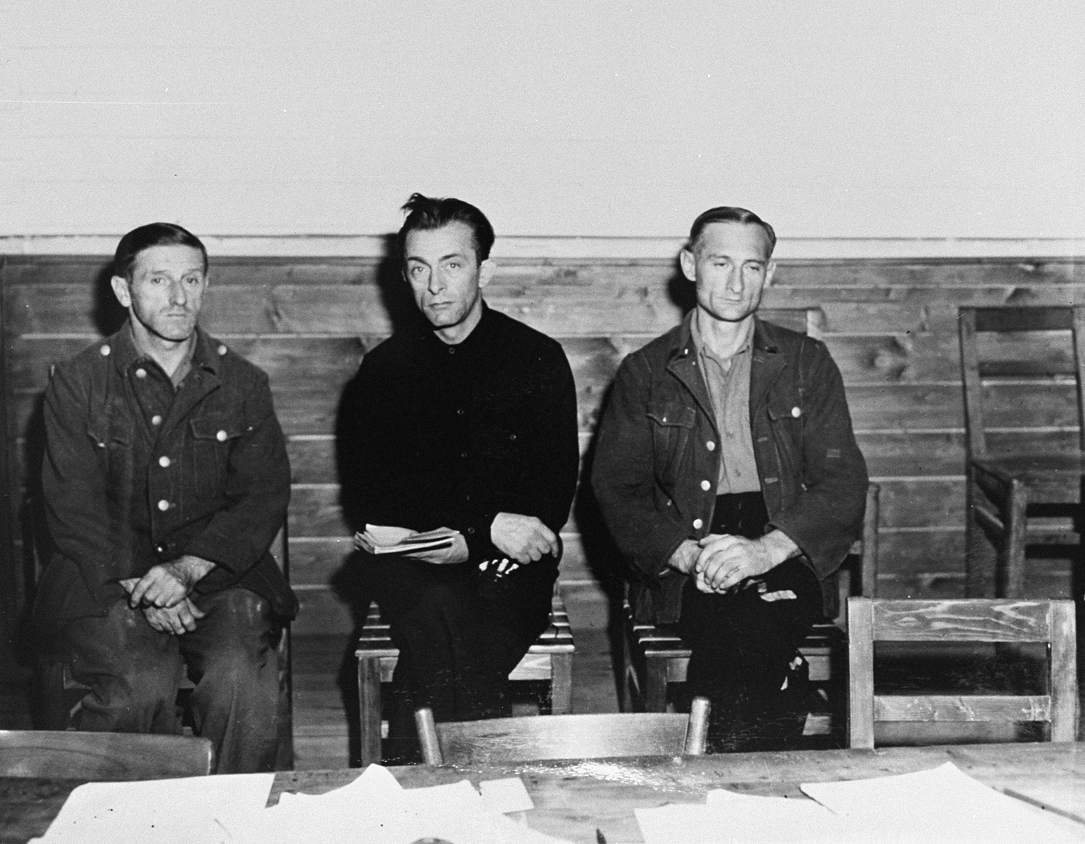 Three prisoners who await trial for murder and mistreatment of prisoners at Gusen, a sub-camp of Mauthausen, sit in on proceedings at the trial of former camp personnel and prisoners from Dora-Mittelbau.