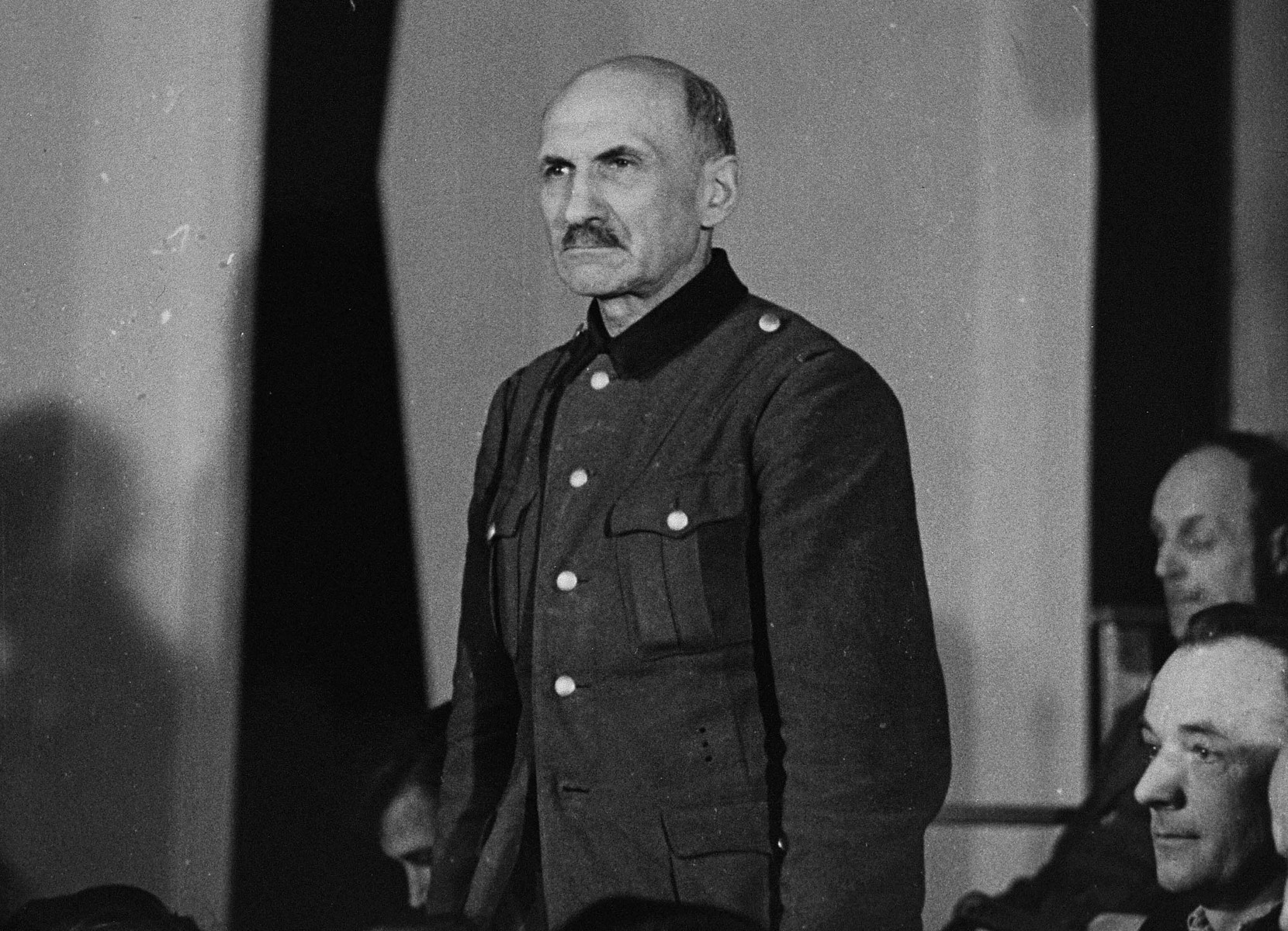 Werner Grahn, a defendant at the trial of 61 former camp personnel and prisoners from Mauthausen, stands in his place in the defendants' dock.