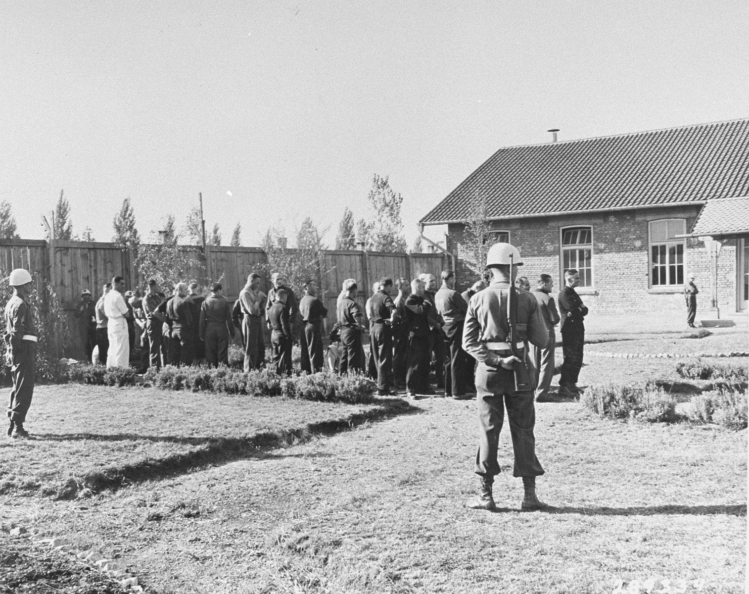 The 31 former camp personnel and prisoners on trial for crimes committed at Buchenwald wait in the courtyard by the courtroom on the day they are to be sentenced.