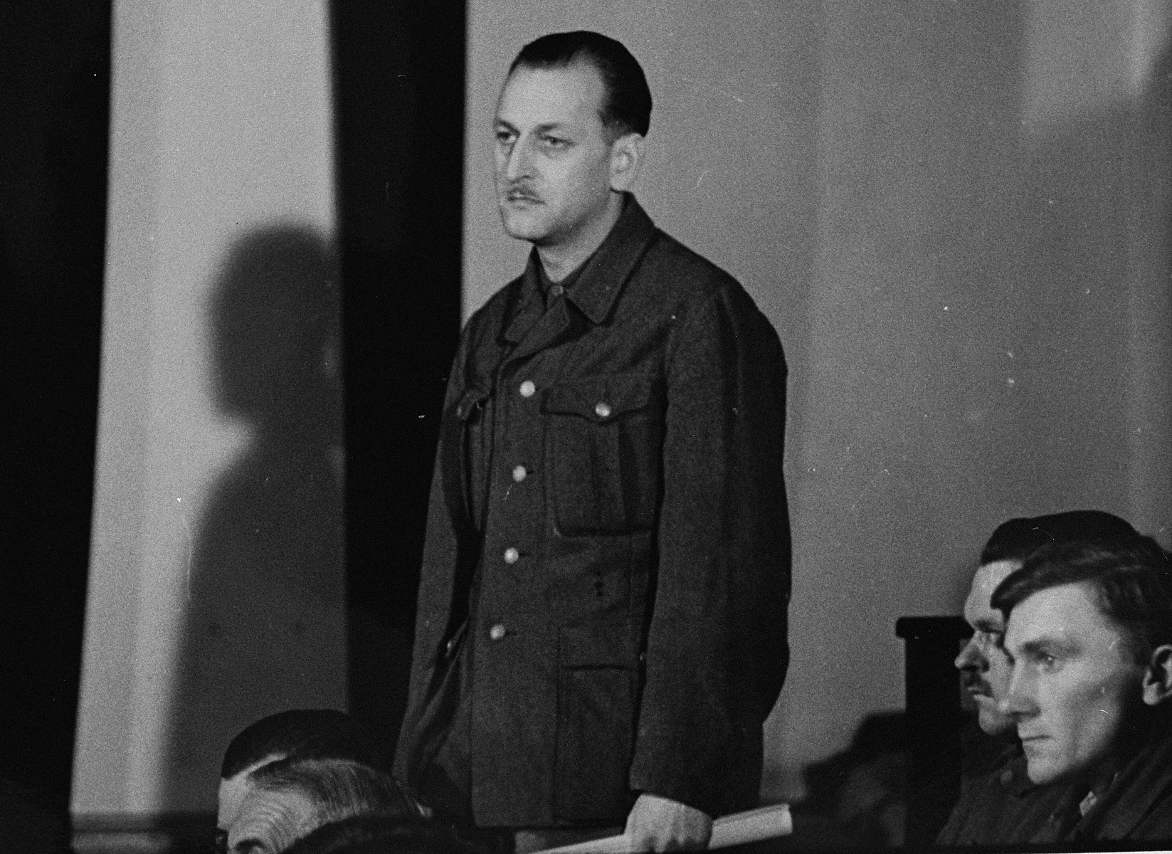 Defendant Gustav Kreindl, at the trial of 61 former camp personnel and prisoners from Mauthausen, stands in his place in the defendants' dock.   Kreindl was a medical orderly at Ebensee, a sub-camp of Mauthausen.  He was accused of selecting incurable patients at the camp infirmary to be exterminated.  He was convicted and executed on May 27, 1946.