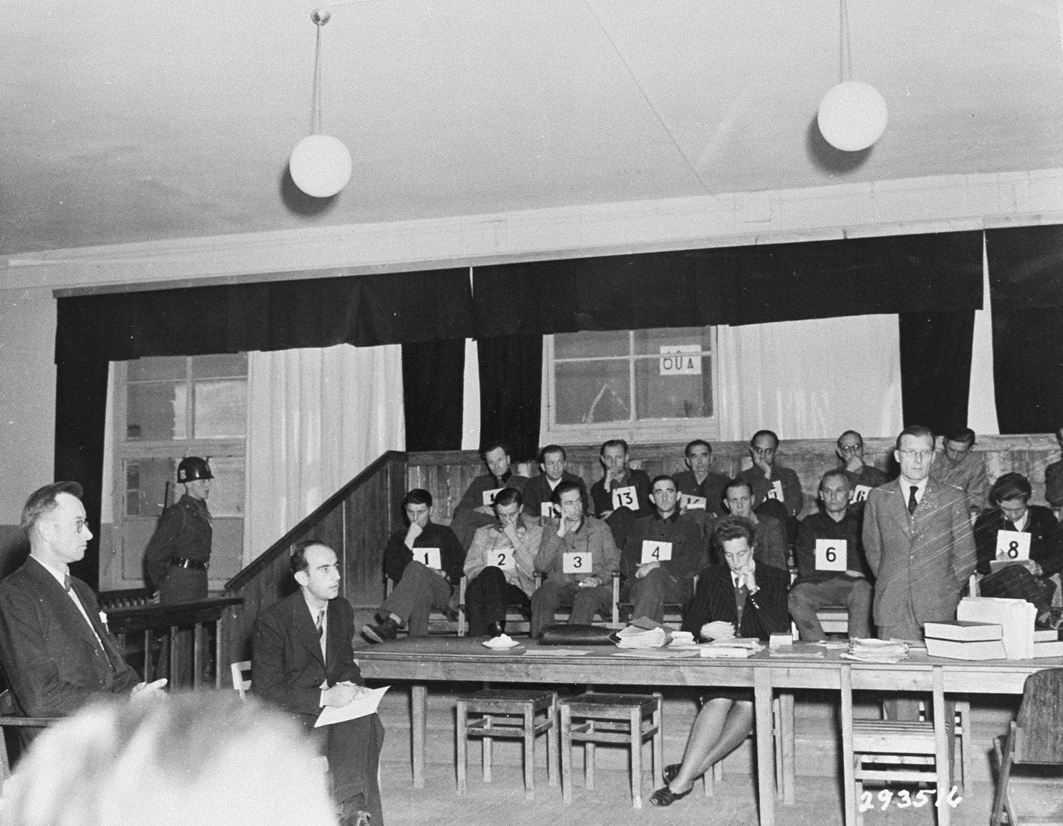 Jan Poslesal (far left), a Czech witness for the defense, begins his testimony at the trial of former camp personnel and prisoners from Dora-Mittelbau.  To his left is interpreter Fred Frankle.