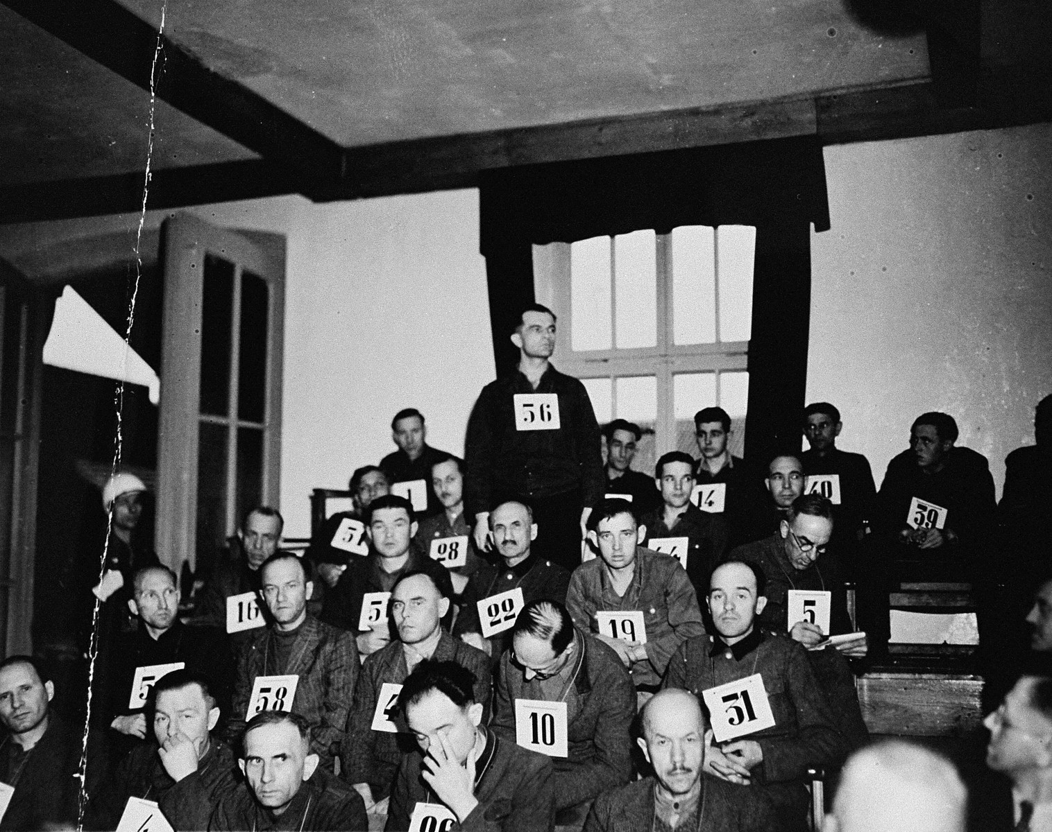 Former SS-Hauptsturmfuehrer Doctor Willi Jobst, a defendant at the trial of 61 former camp personnel and prisoners from Mauthausen, stands in his place in the defendants' dock.  Dr. Jobst was camp physician of the Ebensee concentration camp.  Jobst was convicted and sentenced to death on May 13, 1946.