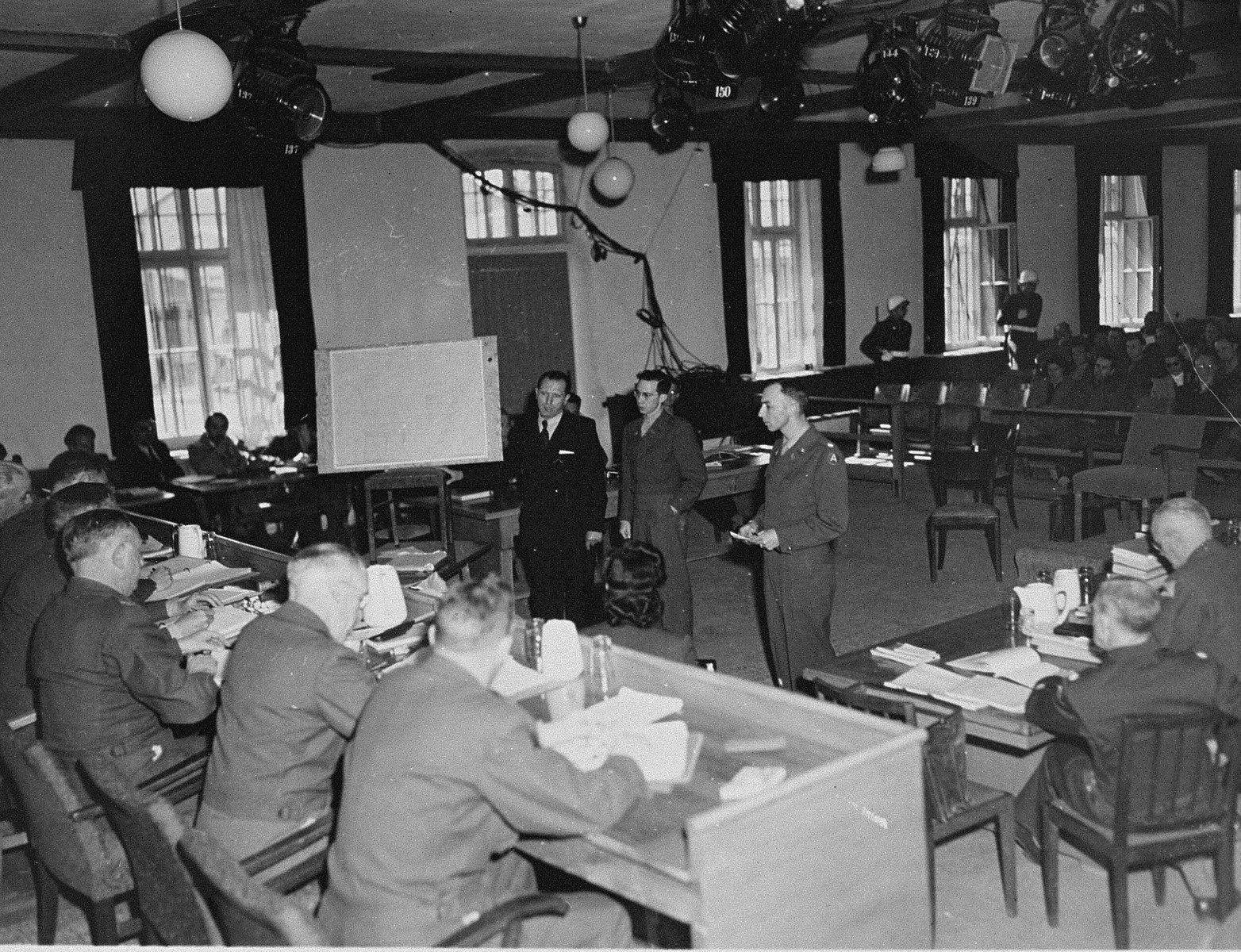 A witness presents evidence to the tribunal at the trial of 61 former camp personnel and prisoners from Mauthausen.  Standing at right is U.S. prosecutor William Denson.