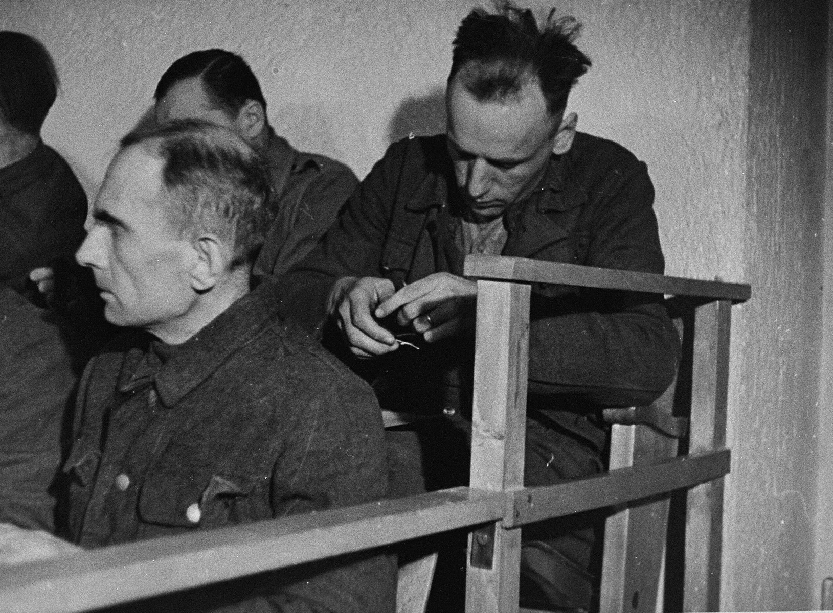 An unidentified defendant at the trial of 61 former camp personnel and prisoners from Mauthausen, sits in his place in the defendants' dock.
