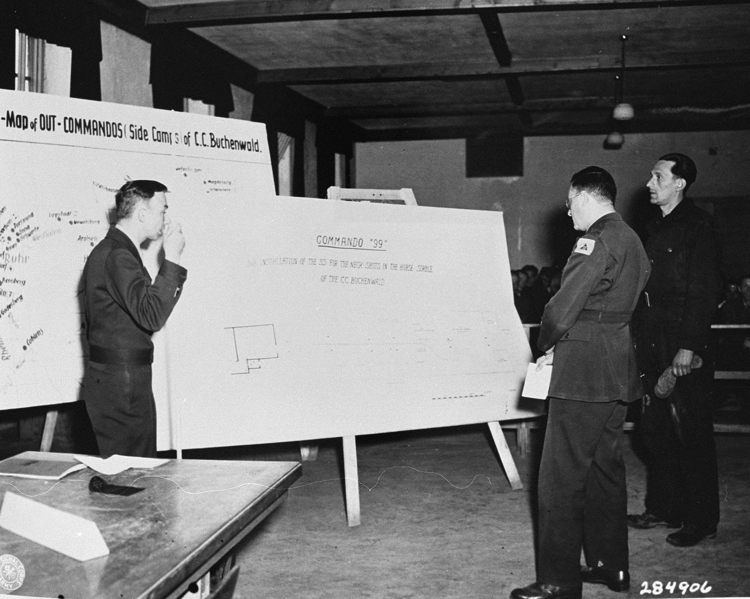 Horst Dittrich (right), a witness for the prosecution, identifies a diagram of a stable where prisoners were shot, at the trial of former camp personnel and prisoners from Buchenwald.   Looking on are lead U.S. Prosecutor William Denson (left) and interpreter Rudloph Nathanson (center).