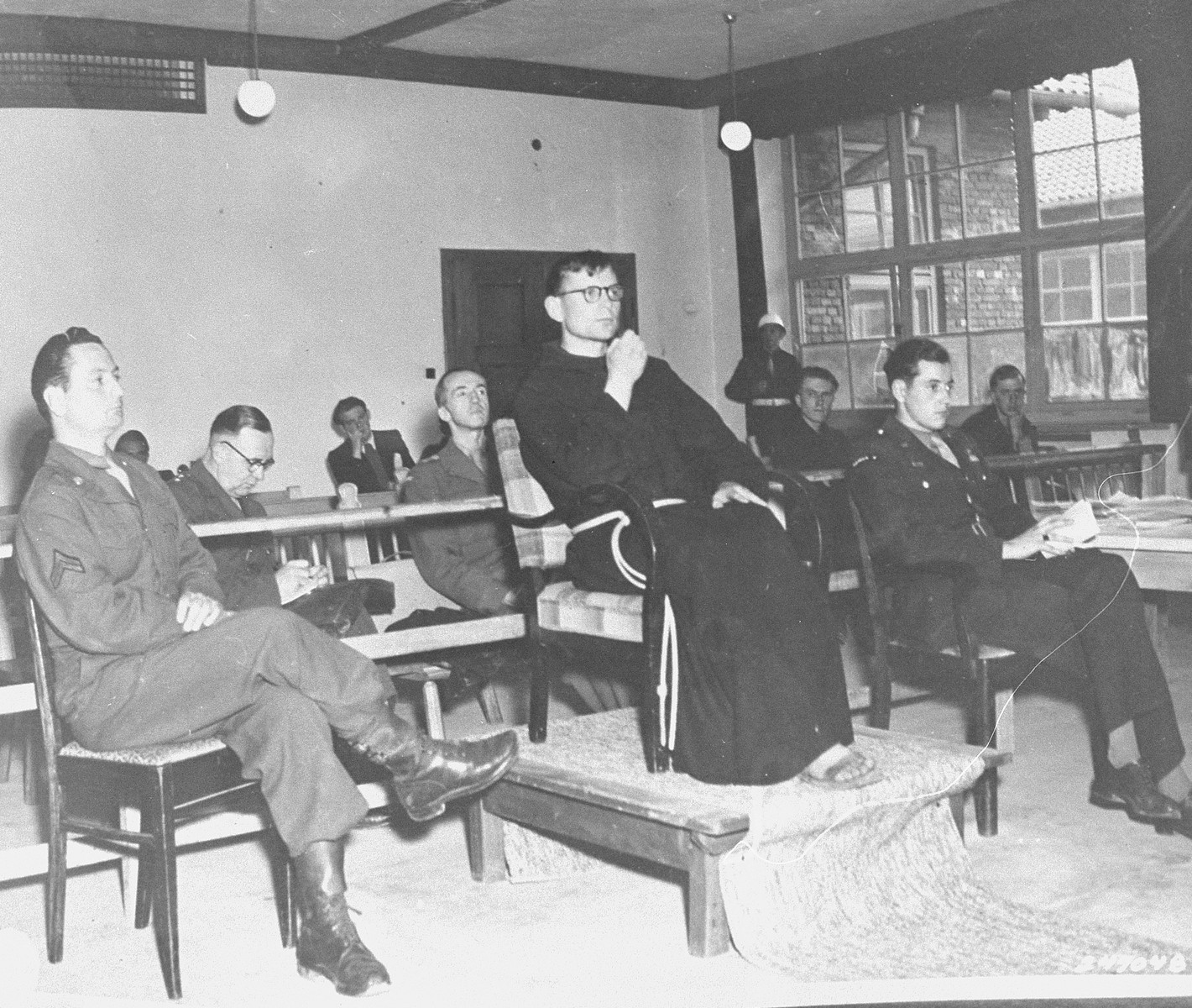 Father Lelere, a former prisoner, testifies at the trial of former camp personnel and prisoners from Flossenbuerg.  On the right is Fred Stecker, a court interpreter.