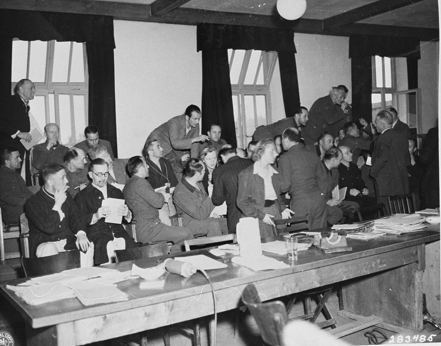 Defendants confer with their defending counselors at the trial of former camp personnel and prisoners from Buchenwald.