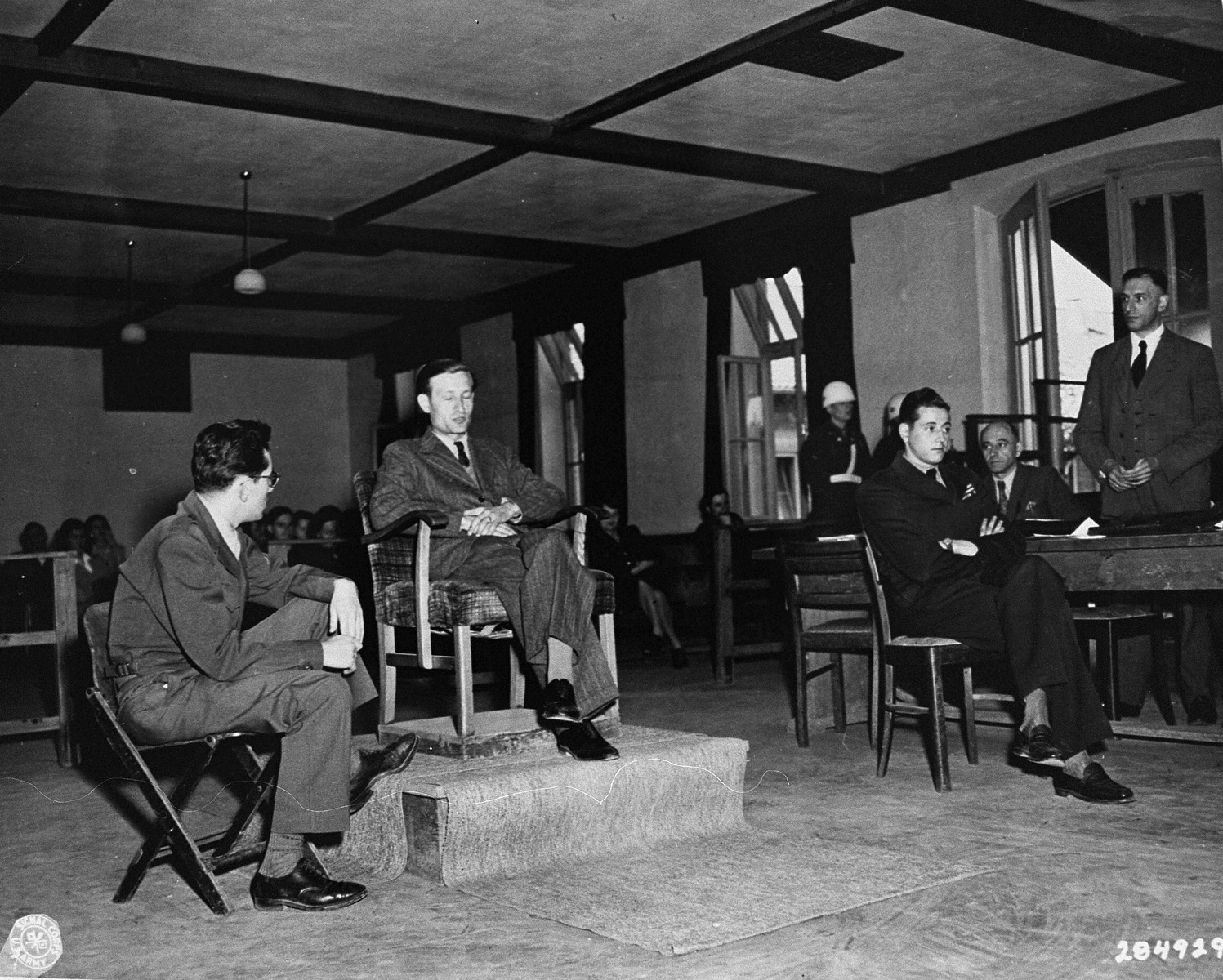A Polish witness for the prosecution testifies at the trial of 31 former camp personnel and prisoners form the Buchenwald concentration camp.    Court personnel pictured from left to right are: Martin Szpigielman, a Polish interpreter; the unidentified Polish witness; Fred Stecker, a German interpreter; and Dr. Richard Wacker, a defense attorney (standing).