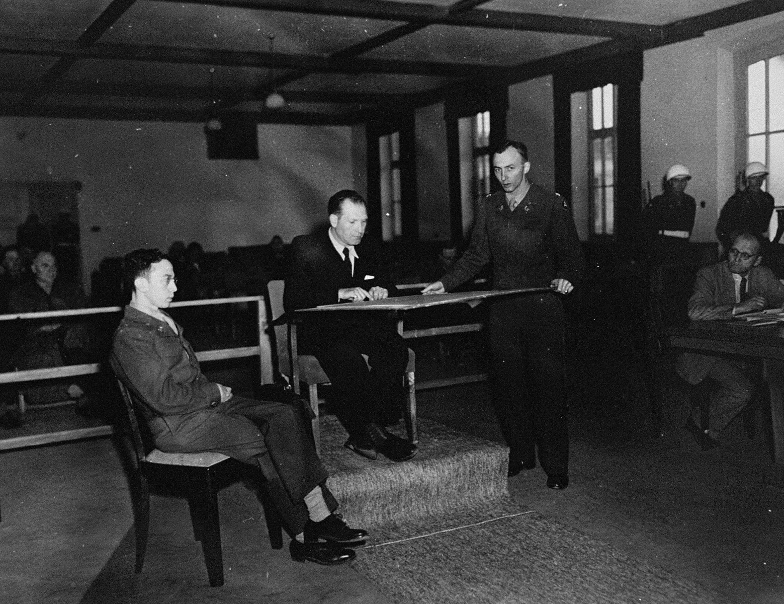 A witness testifies at the trial of 61 former camp personnel and prisoners from Mauthausen.    Pictured on the right is U.S. prosecutor William Denson.