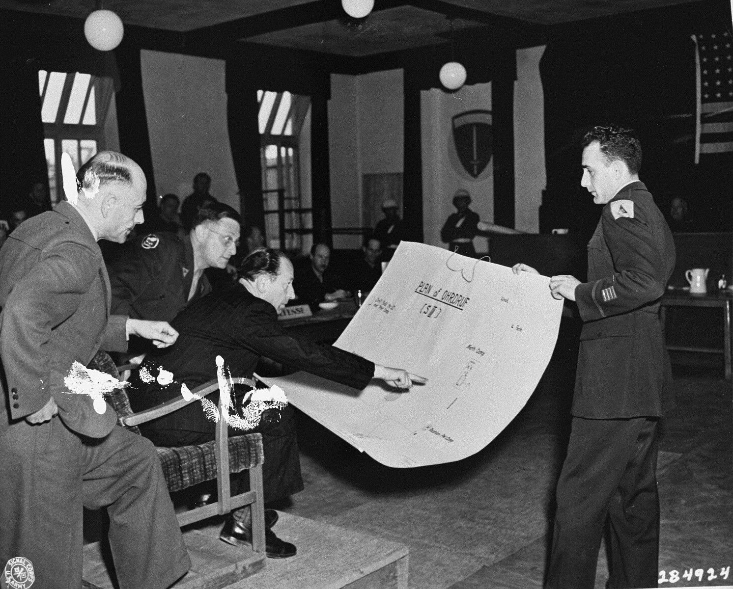 Dr. Viktor Abend, a Polish civilian witness for the prosecution at the trial of former camp personnel and prisoners from Buchenwald, points to a diagram of Ohrdruf, a sub-camp of Buchenwald.    Court personnel pictured from left to right are Dr. Aheimer, a defense attorney; Rudolph Nathanson, an interpreter; Dr. Abend; and Sol Surowitz, an attorney for the prosecution.