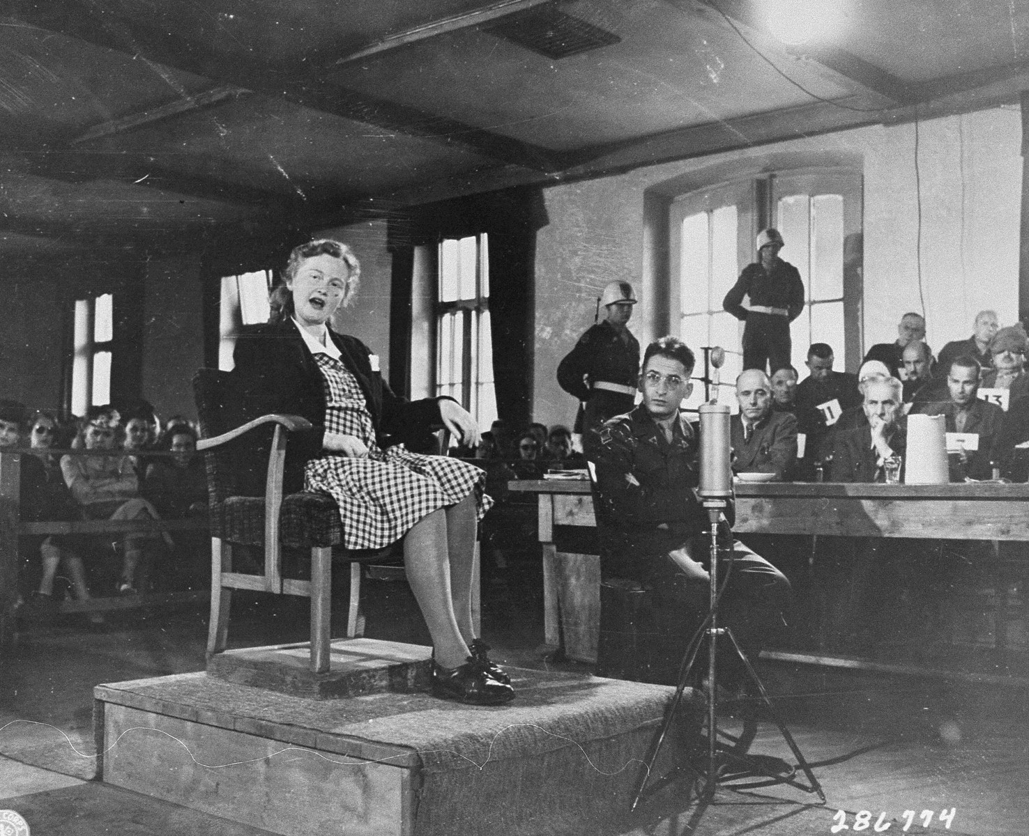 Ilse Koch testifies in her own defense at the trial of former camp personnel and prisoners from Buchenwald.    To her left is Herbert Rosenstock, an interpreter.