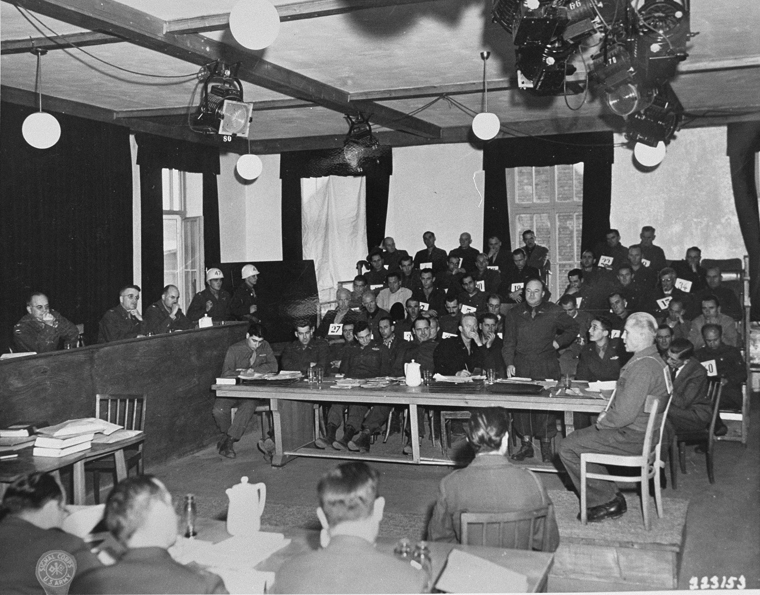 Defendant Otto Schultz replies to a question put to him by defense attorney Capt. John May (standing), at the trial of former camp personnel and prisoners from Dachau.