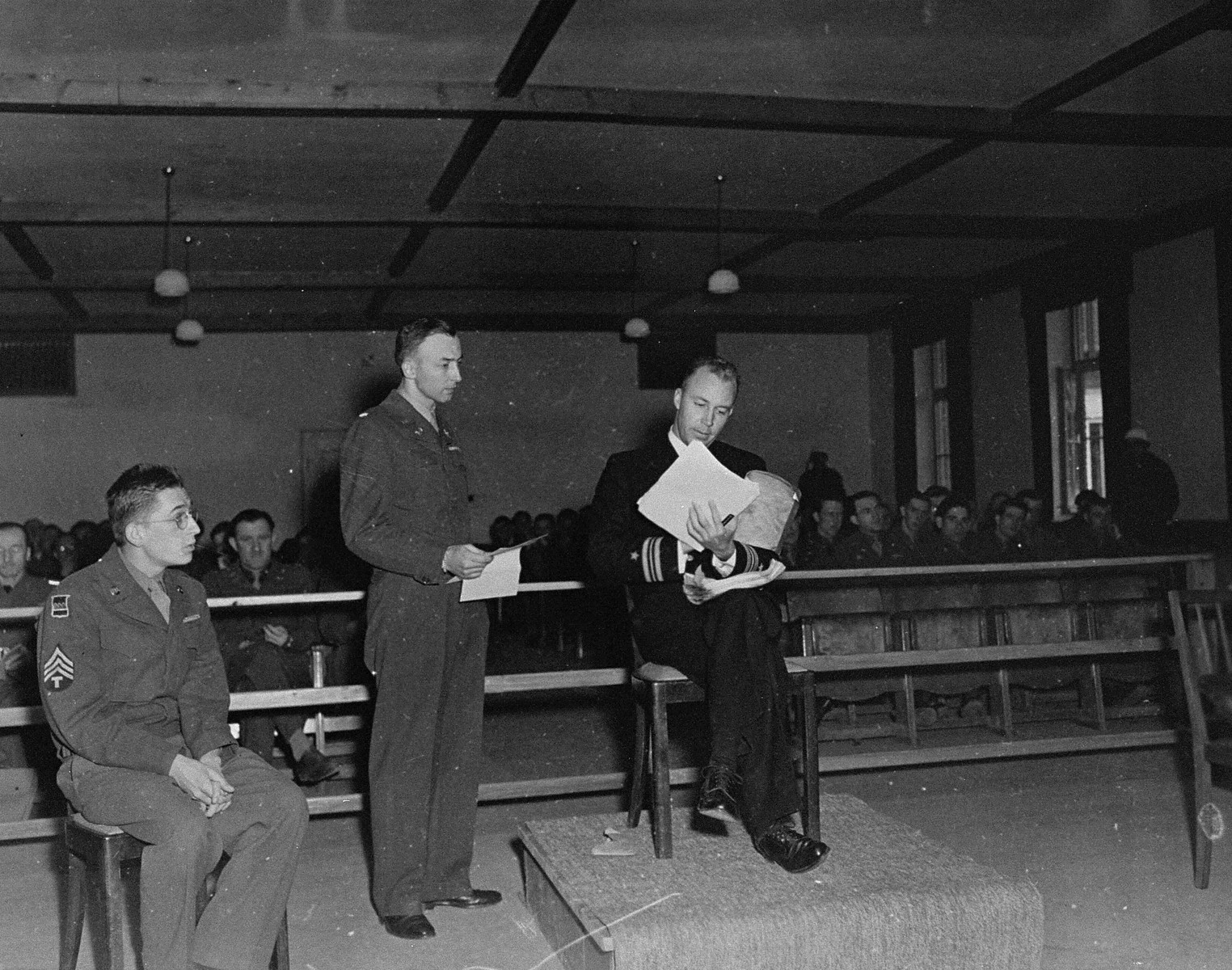 A witness testifies for the prosecution at the trial of 61 former camp personnel and prisoners from Mauthausen.    Testifying is Lieutenant Jack Taylor (b. 1908).  Lt. Taylor served in the OSS (American Secret Service).  He was captured by the Germans and imprisoned in Mauthausen.  Also pictured are Herbert Rosenstock, an interpreter (far left) and U.S. prosecutor William Denson (middle).