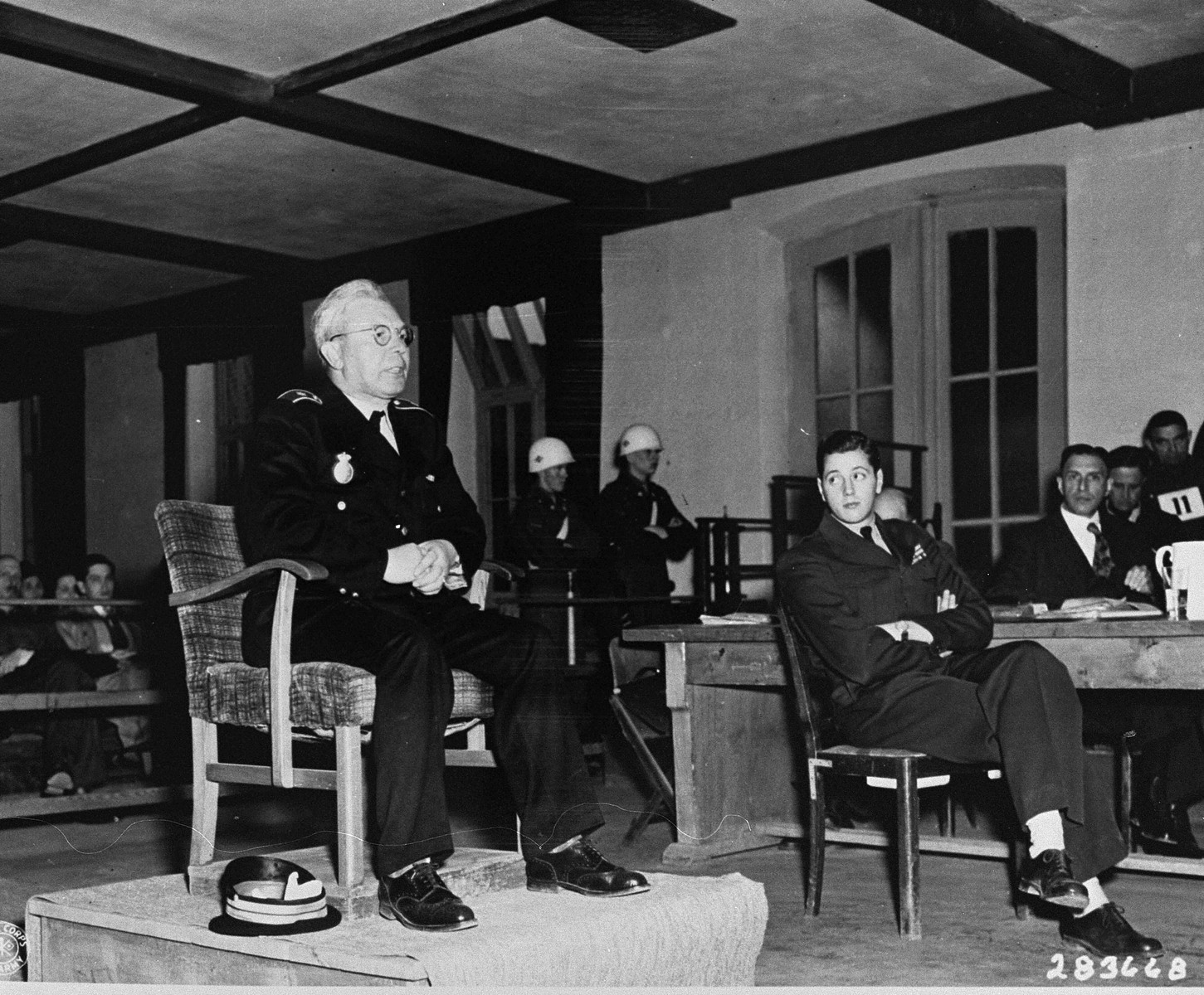 Major Flakenberg, a member of the Danish police, testifies for the prosecution at the trial of former camp personnel and prisoners from Buchenwald.  To his left is Fred Stecker, an interpreter.