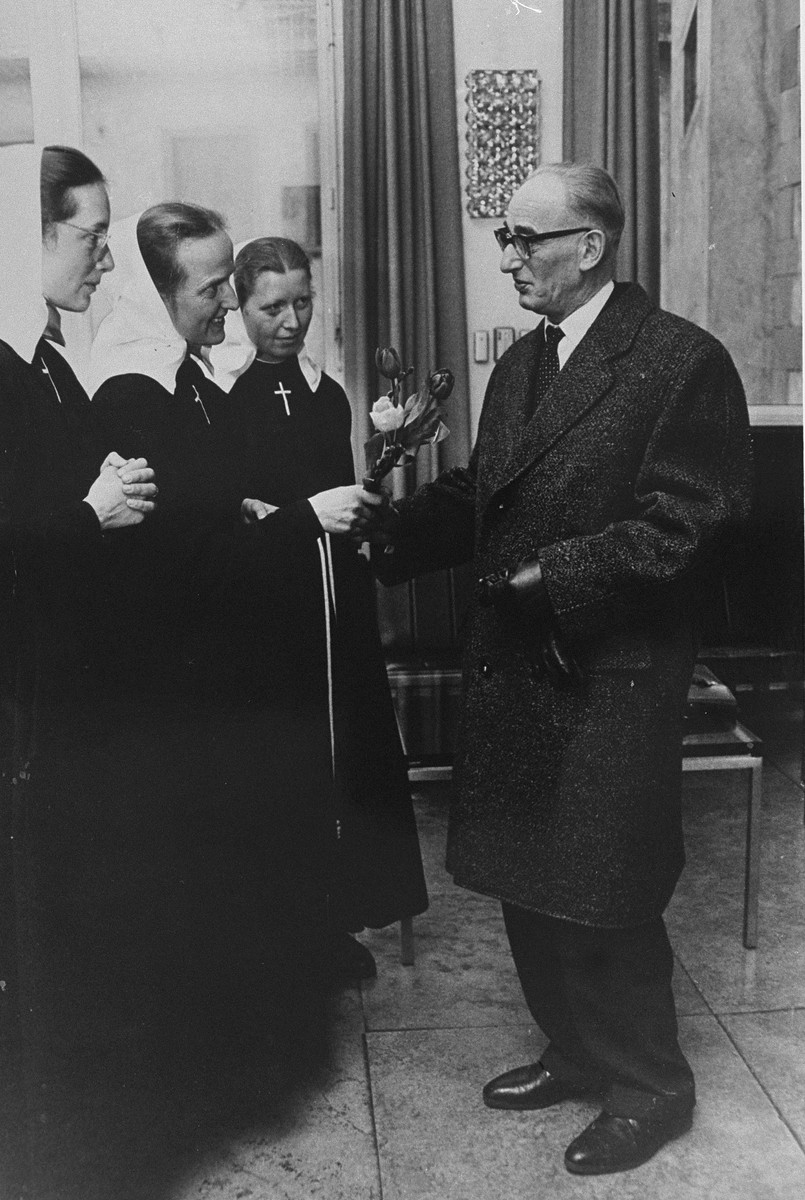 Dr. Otto Wolken receives flowers from a group of nuns before testifying as a witness at the International Military Tribunal at Nuremberg.