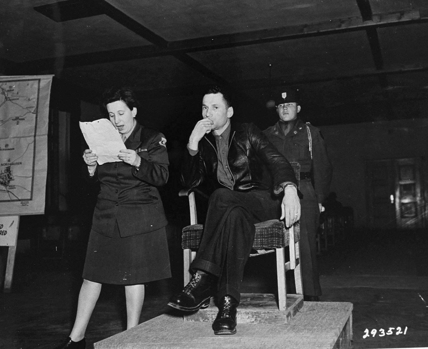 Willi Zwiener, a kapo who turned against his fellow defendants, testifies through an interpreter at the trial of former camp personnel and prisoners from Dora-Mittelbau.  To his left the interpreter, Nelly Singer, reads Zwiener's written statement, while behind him stands his guard, Pfc. Ernest Westerrode.