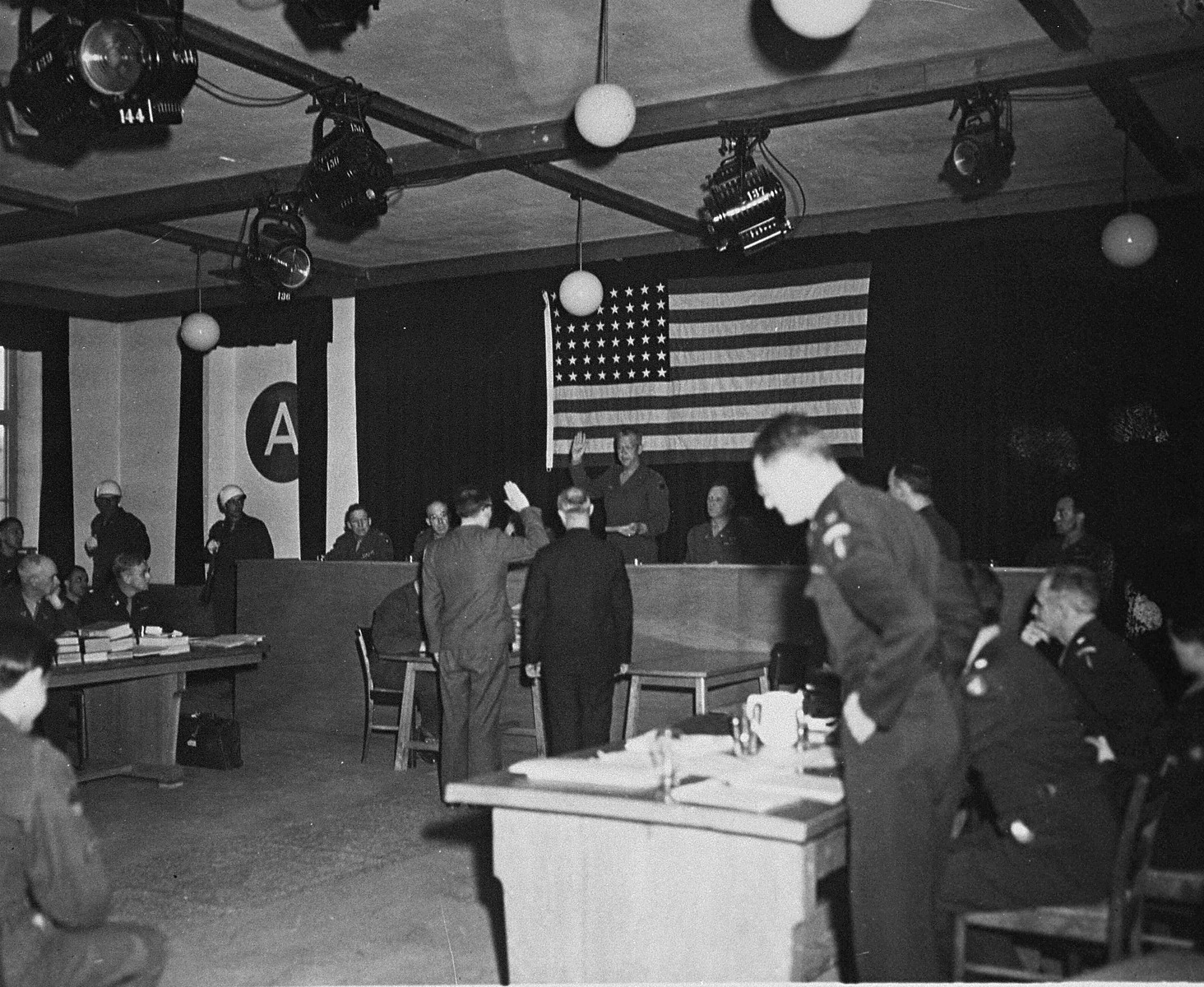 A witness is sworn in at the trial of 61 former camp personnel and prisoners from Mauthausen.  Swearing him in is Major General Fay Brink Prickett, the President of the Military Tribunal.