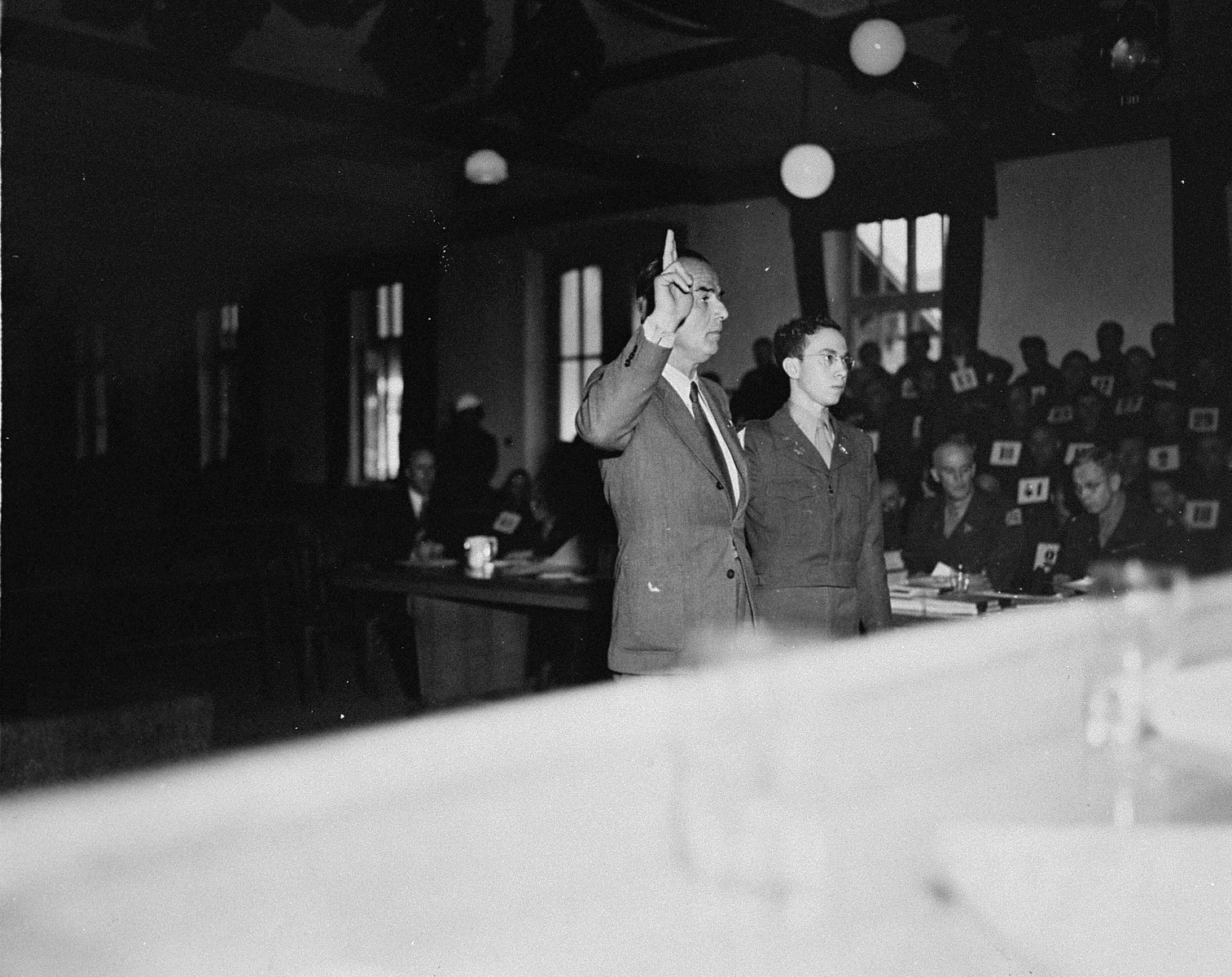 A witness is sworn in at the trial of 61 former camp personnel and prisoners from Mauthausen.