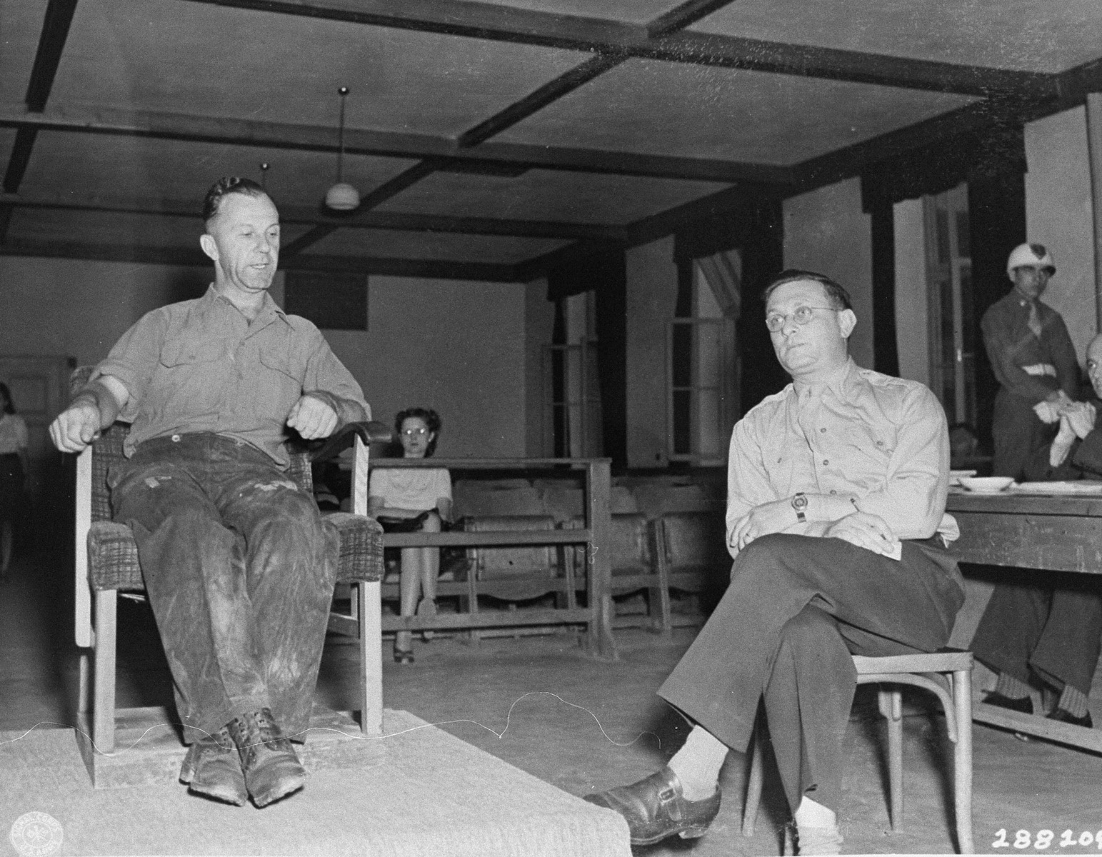 Hermann Grossmann, a former SS lieutenant, testifies in his own defense at the trial of 31 former camp personnel and prisoners from Buchenwald.  On the right is the interpreter, Rudolph Nathanson.