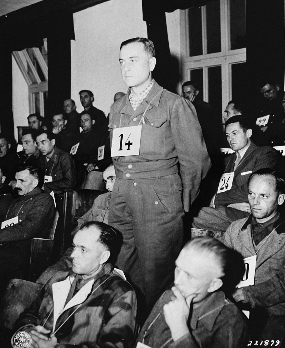 "Dr. Hans Kurt Eisele listens to an account of his pursuits as a Luftwaffe medical researcher at Dachau, where he used prisoners of war as ""human guinea pigs"" to check the effects of extreme pressures and air temperatures, causing numerous fatalities.  Eisele is on trial with 39 other camp personnel and prisoners fom Dachau."