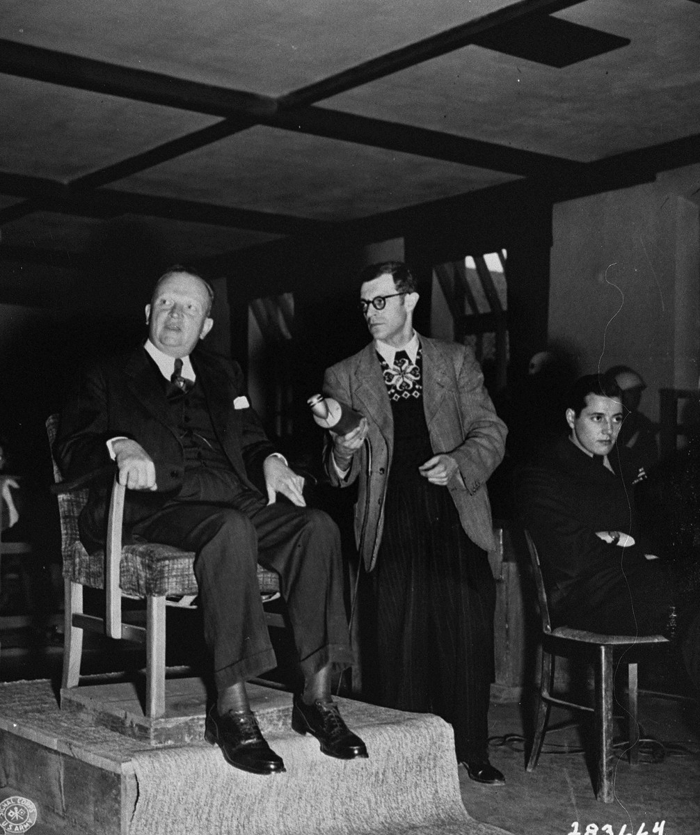 Karl Berthold testifies for the prosecution at the trial of former camp personnel and prisoners from Buchenwald.  To his left is Werner Klein, a radio reporter, and Fred Stecker, an interpreter.