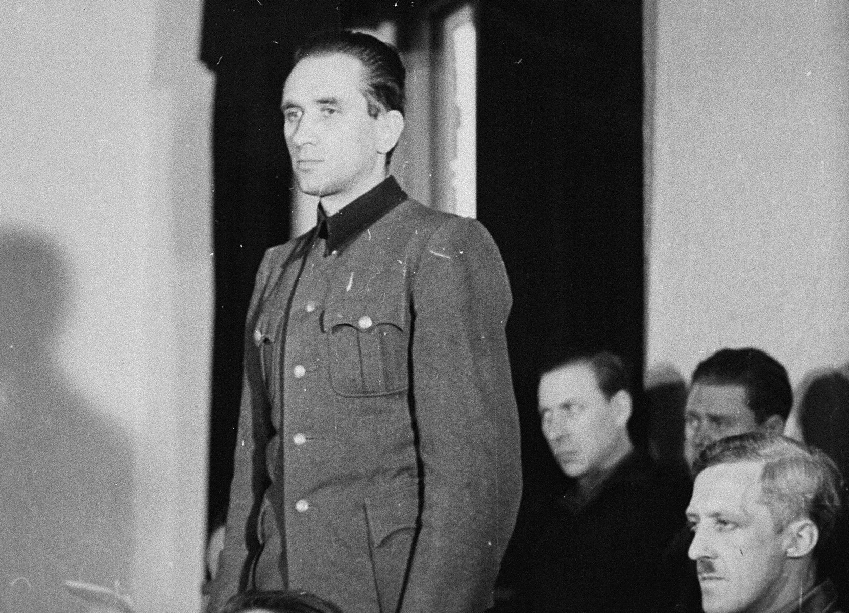 Dr. Friedrich Entress, defendant at the trial of 61 former camp personnel and prisoners from Mauthausen, stands in his place in the defendants' dock.