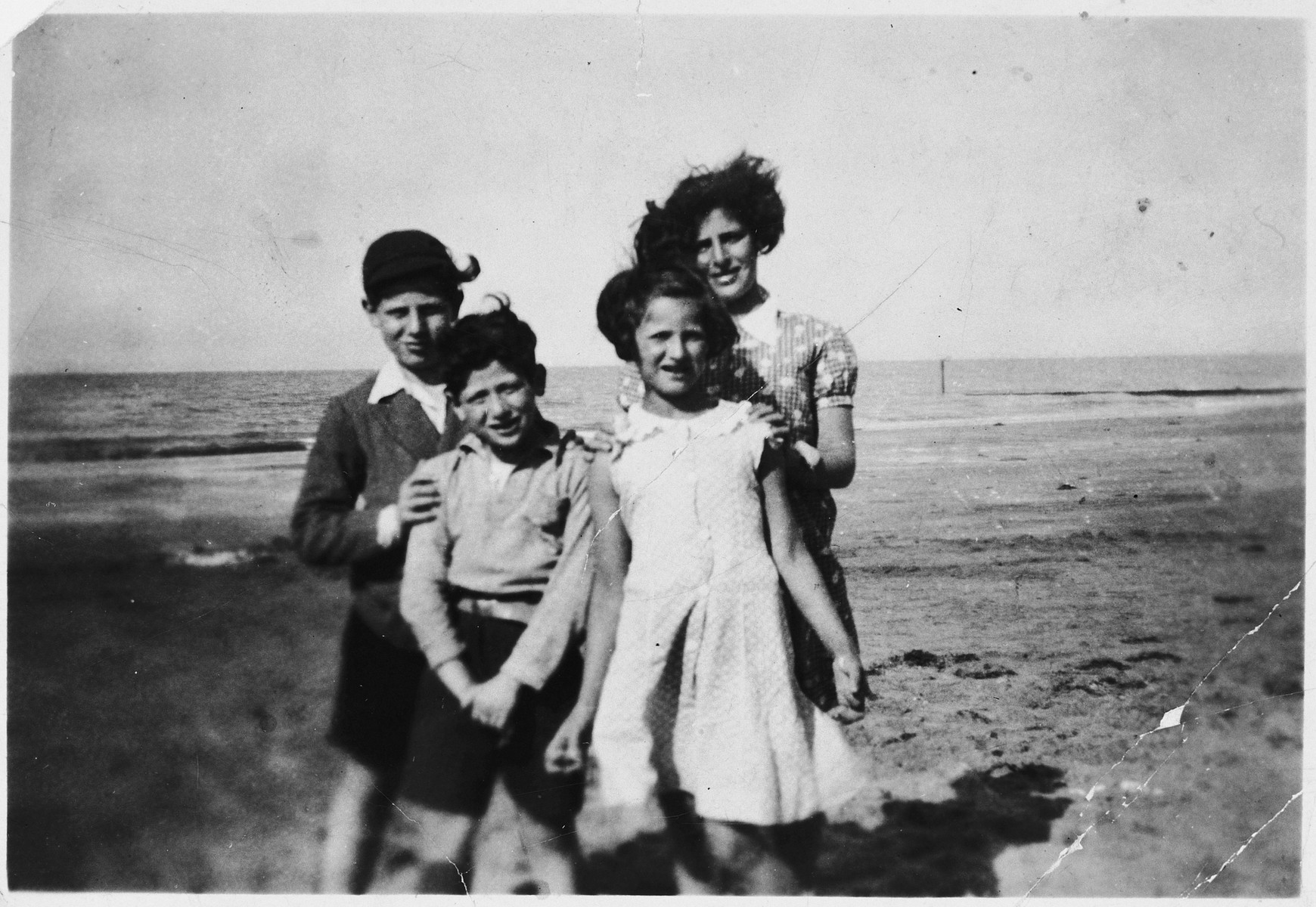 Four siblings pose together on a beach approximately half a year after arriving in England on a Kindertransport.  Pictured are Jacob, Joseph, Anni and Henni Zajac.